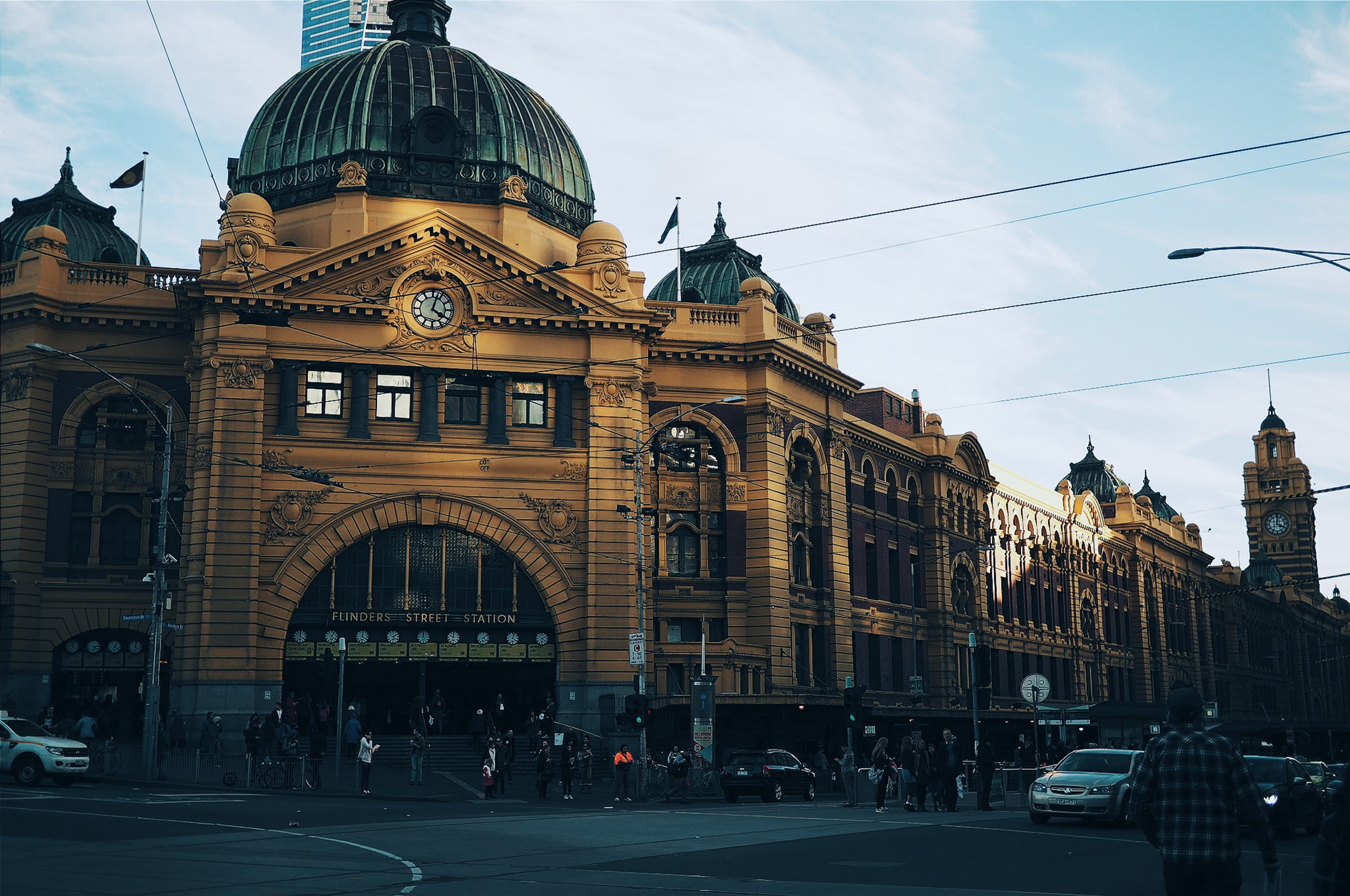 Cars on driving on road in front of Flinders Street Railway Station on clear day