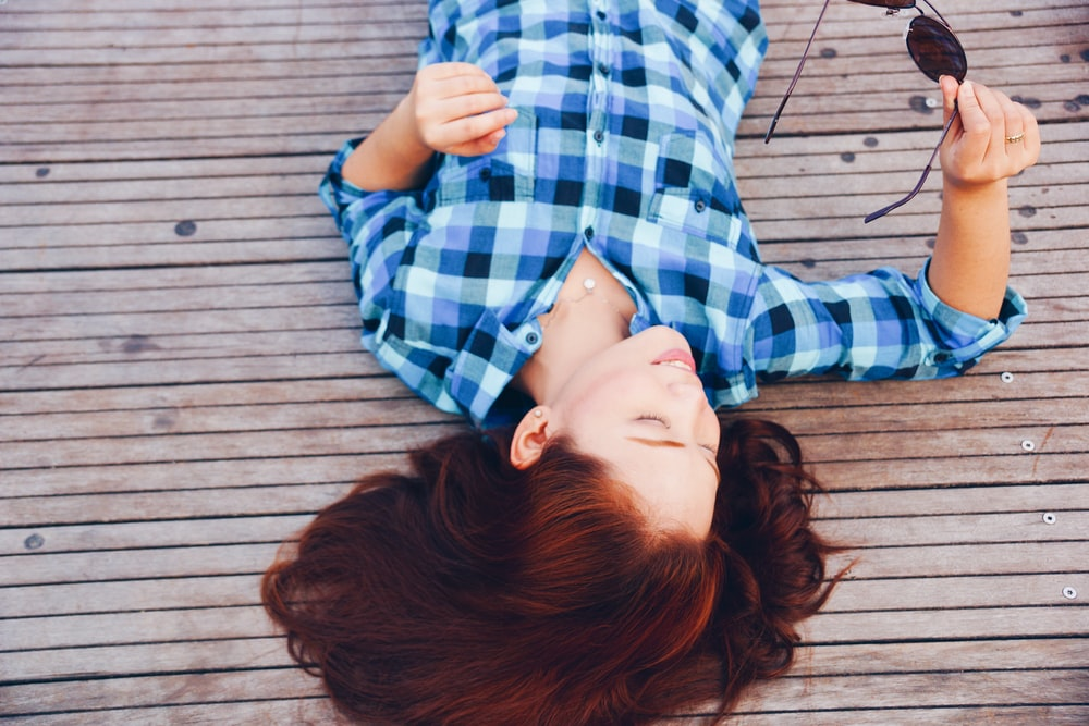 woman in blue flannel shirt laying on floor