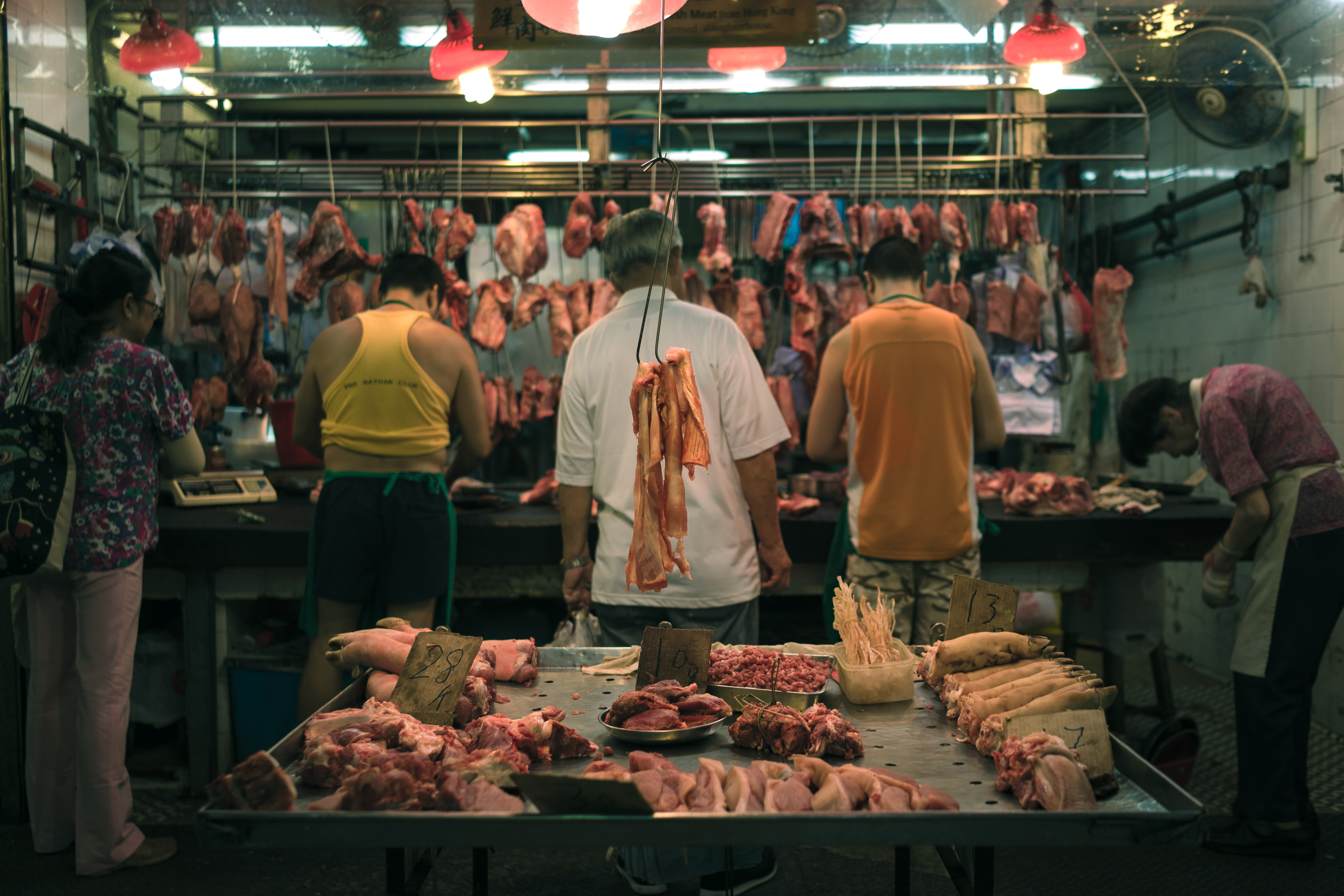 People working at the butchers' with pieces of meat suspended from a railing around them