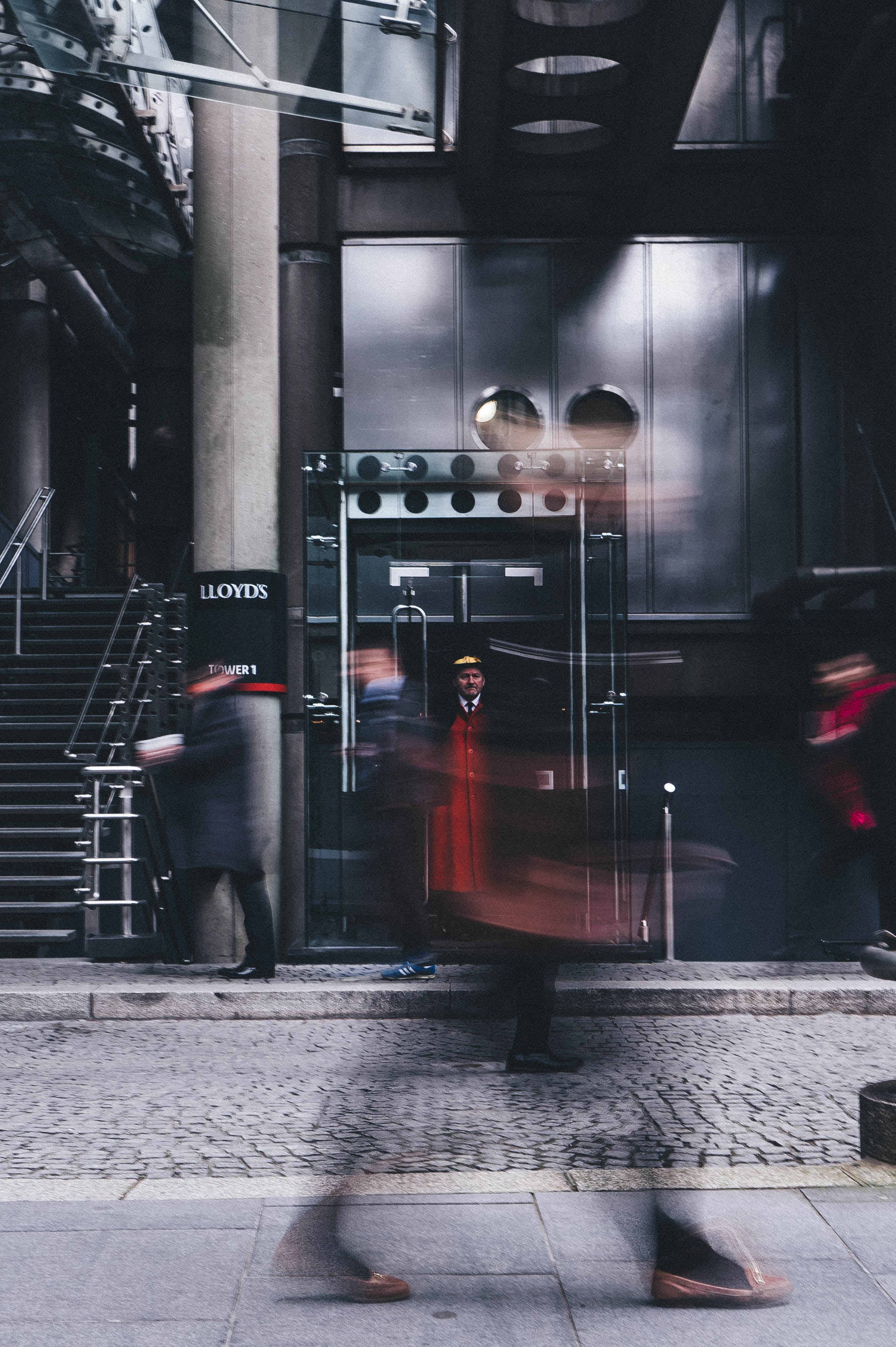 A doorman watching people pass by on Leadenhall Street