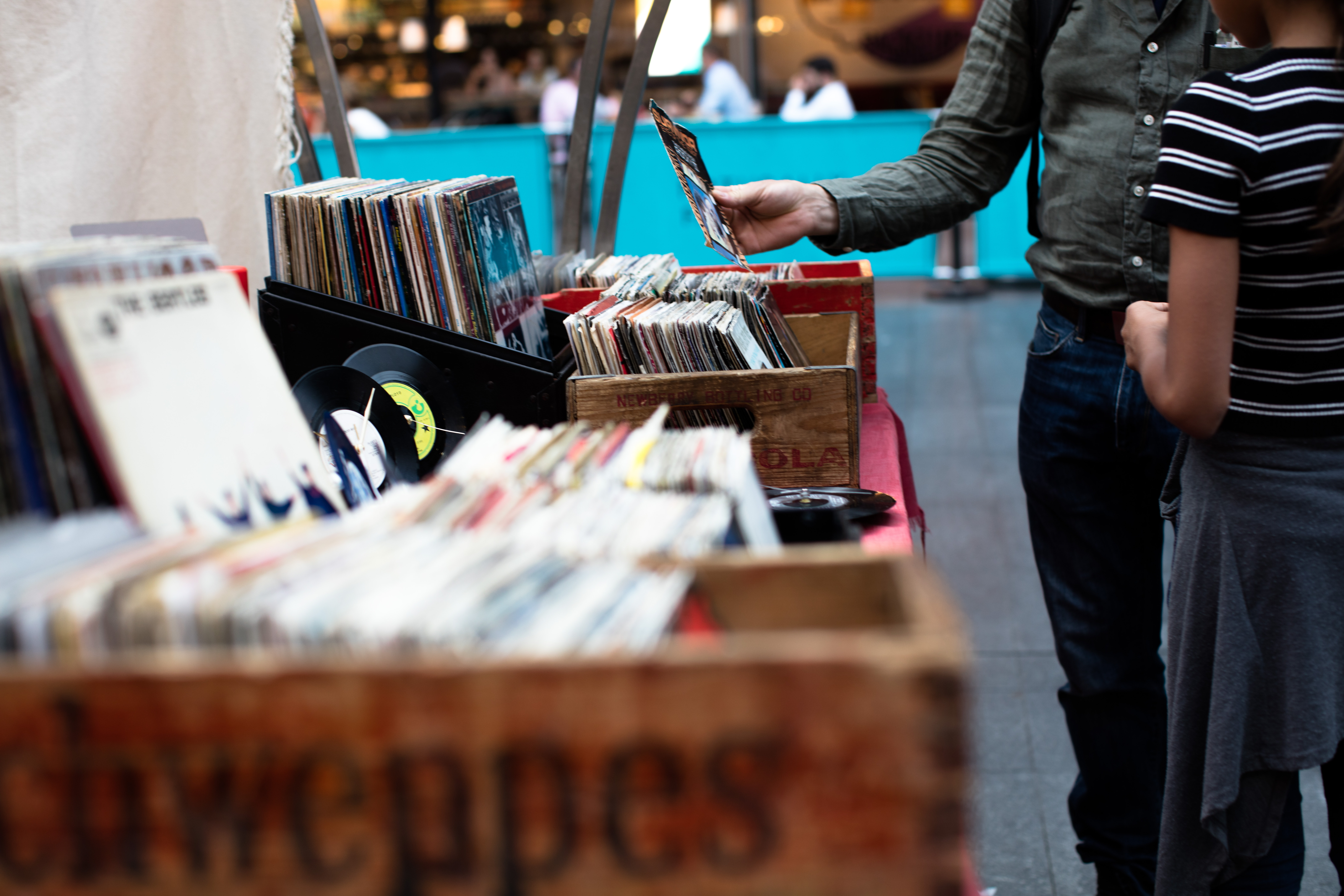 A man and a child browsing vinyl records from vintage boxes