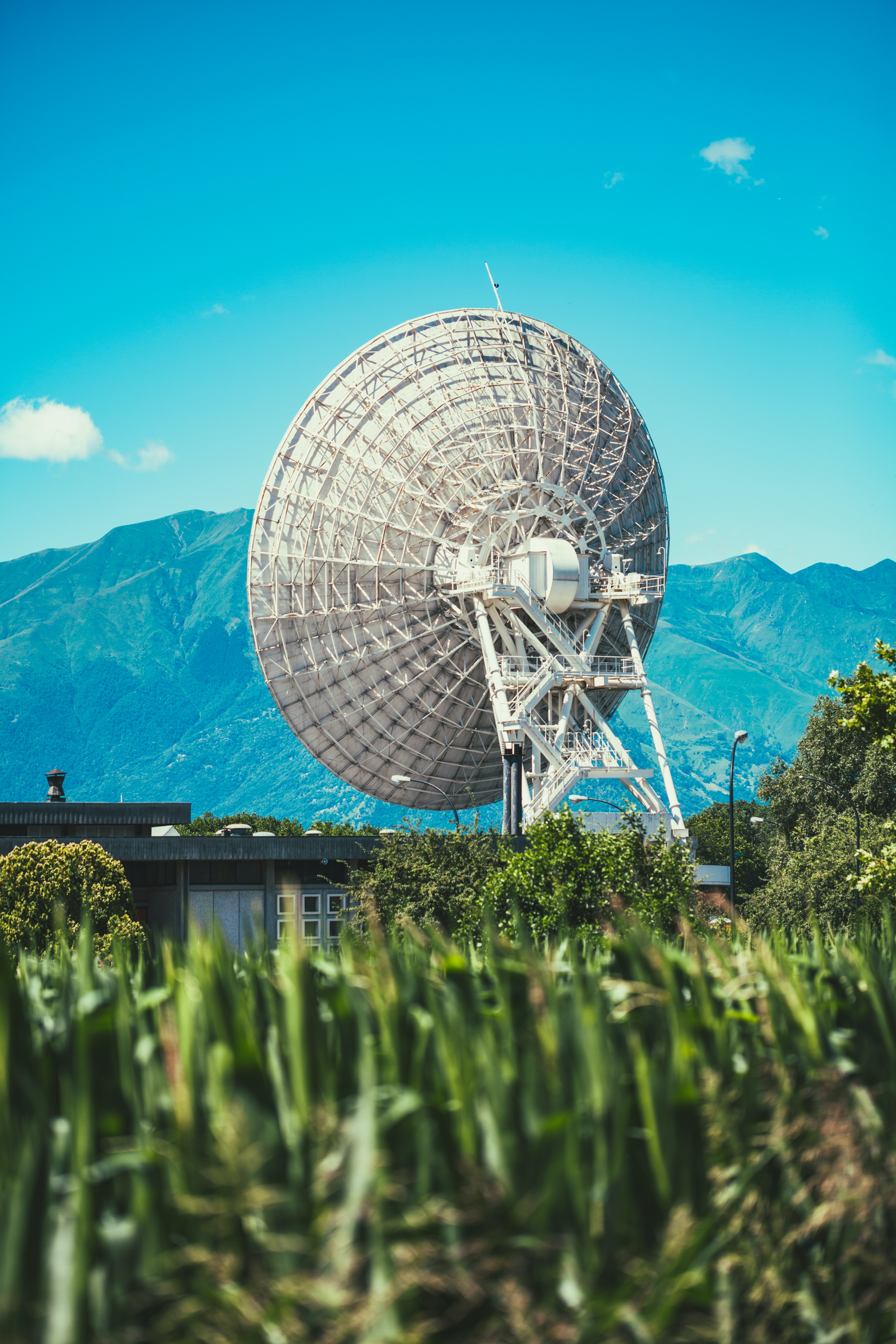 Communication satellite in a grassy field near the mountains