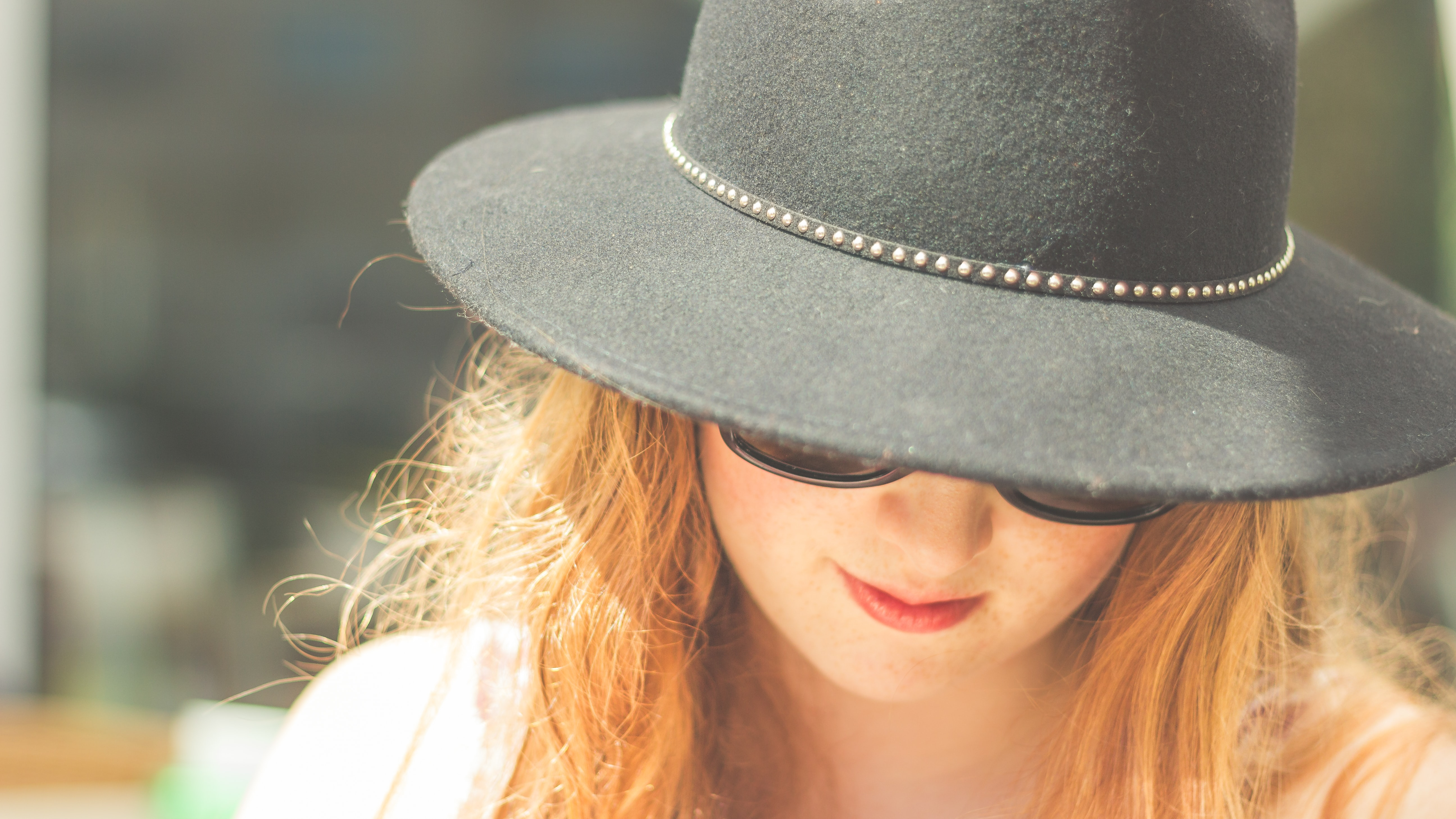 woman looking down wearing black bowler hat