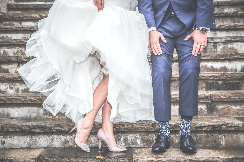 A married couple shows off their wedding dress and suit on steps.