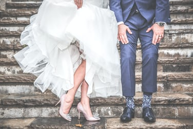 A Married Couple Shows Off Their Wedding Dress And Suit On Steps