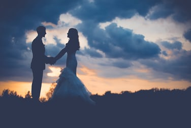 Just Married Bride And Groom Hold Hands On A Hill At Sunset