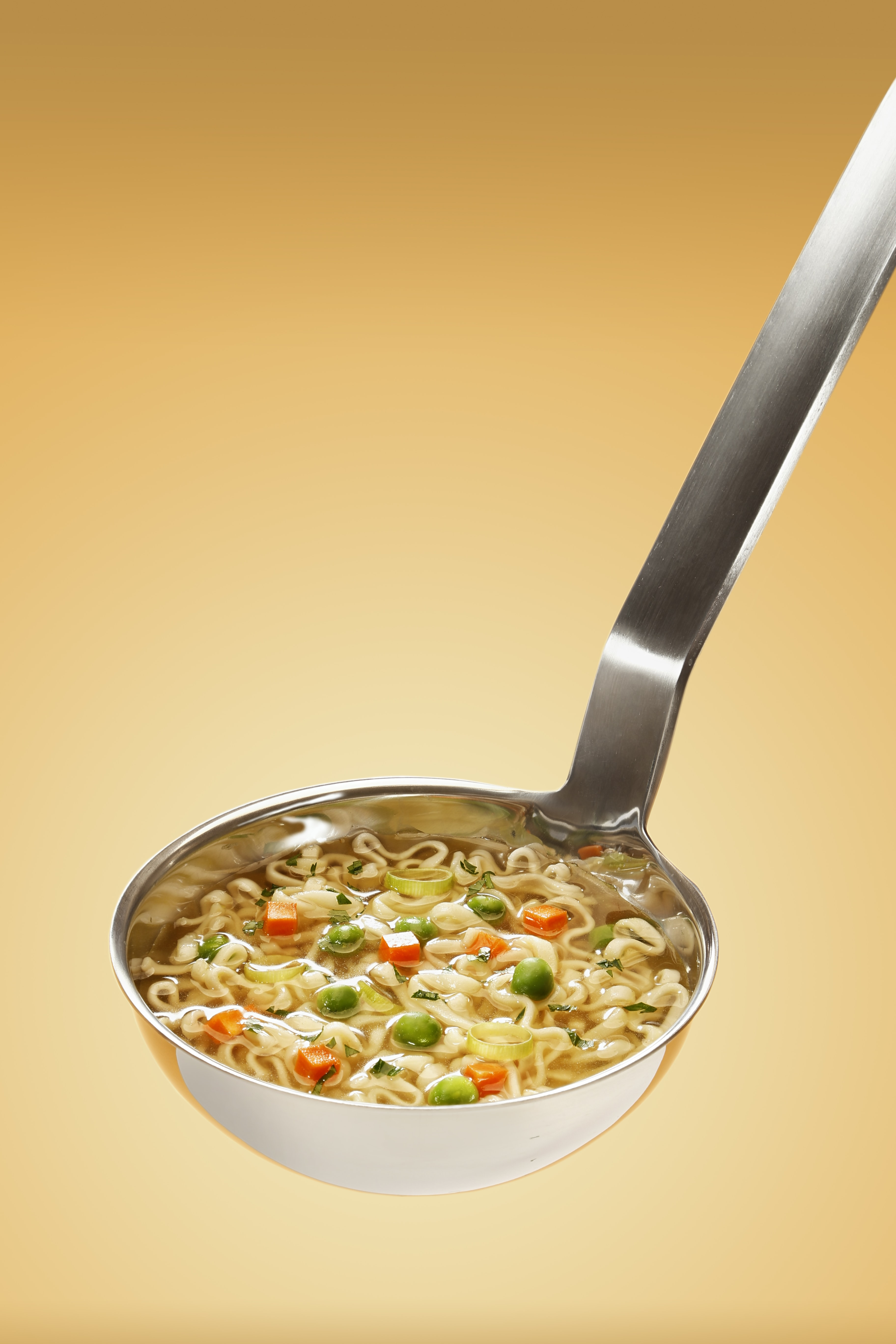 Ladle full of vegetable soup with carrots, peas, and ramen noodles