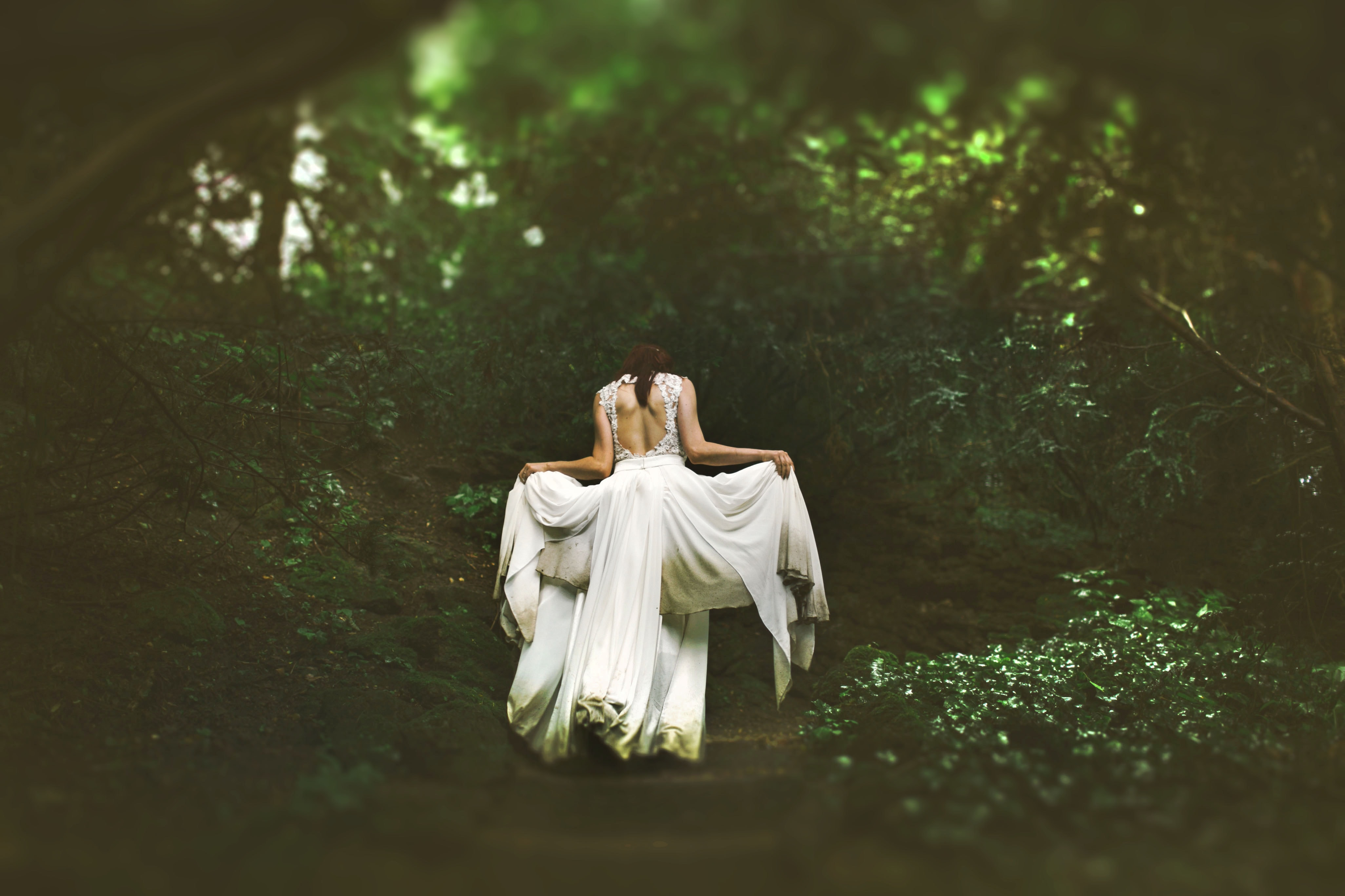 A woman lifting up the ends of her white wedding dress on a forest path