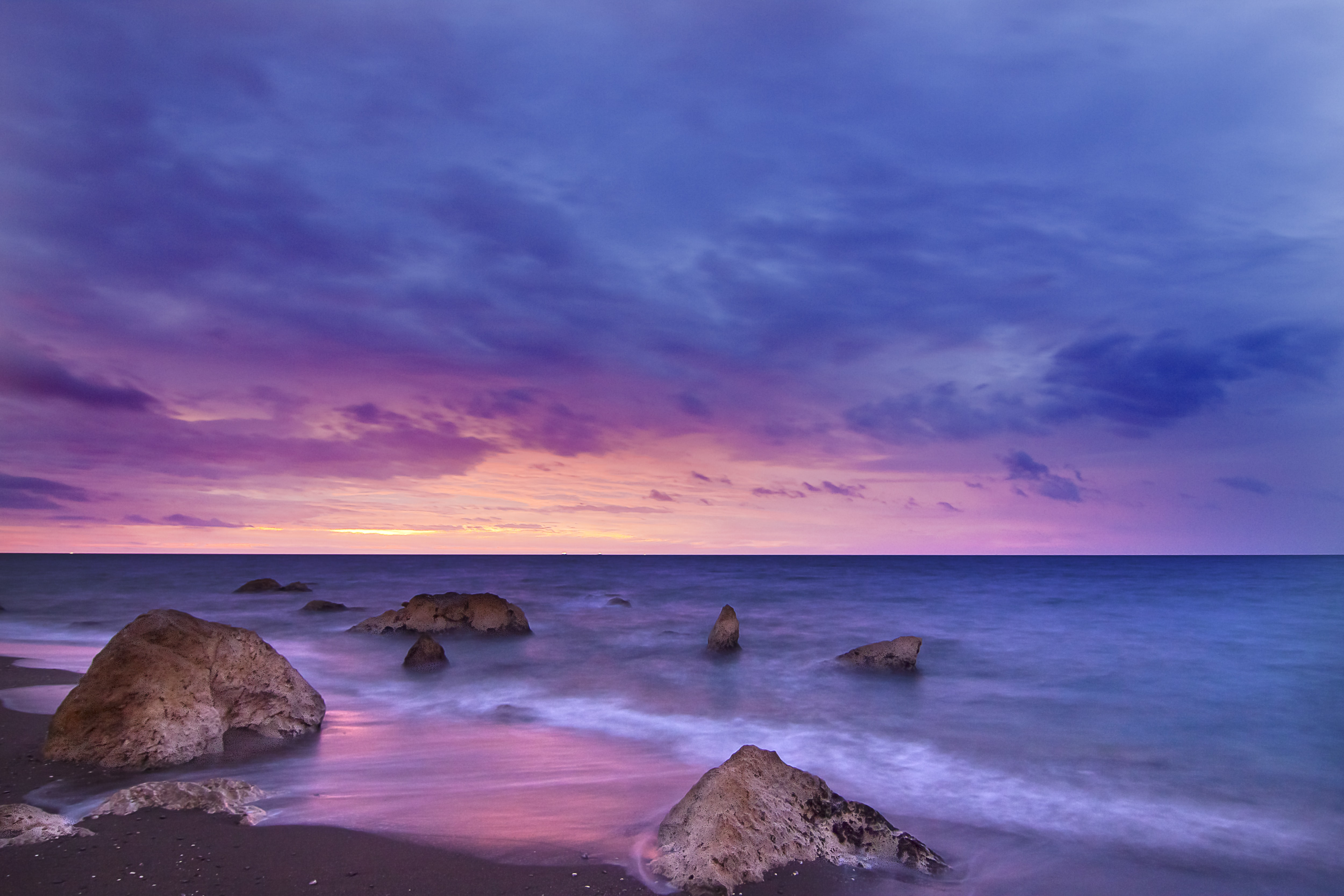 Rocks sit in a calm sea at twilight as the sunset creates a pink, purple, and navy sky at Playa del Peñón del Cuervo.