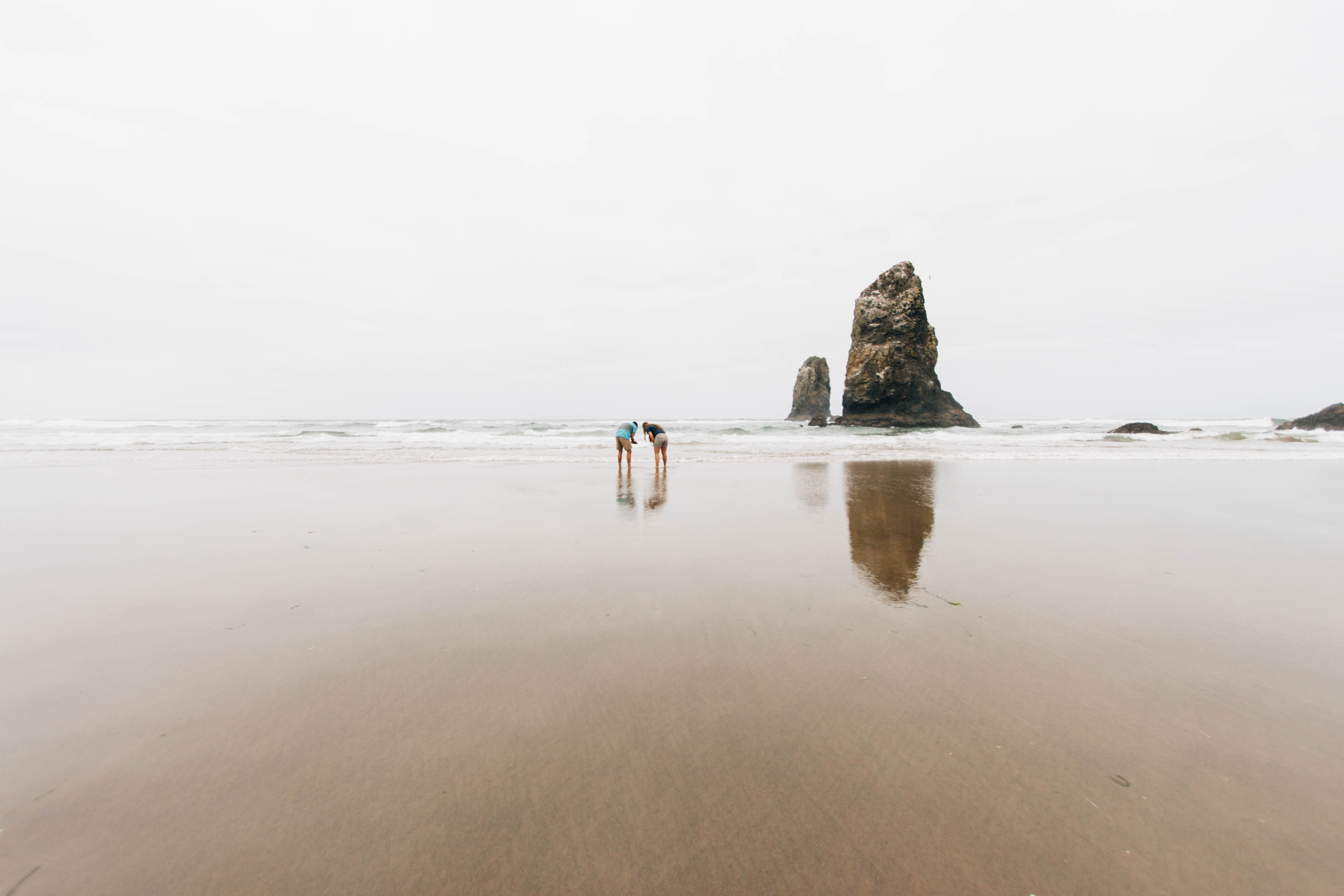 Two persons standing on a wet sand beach in Oregon