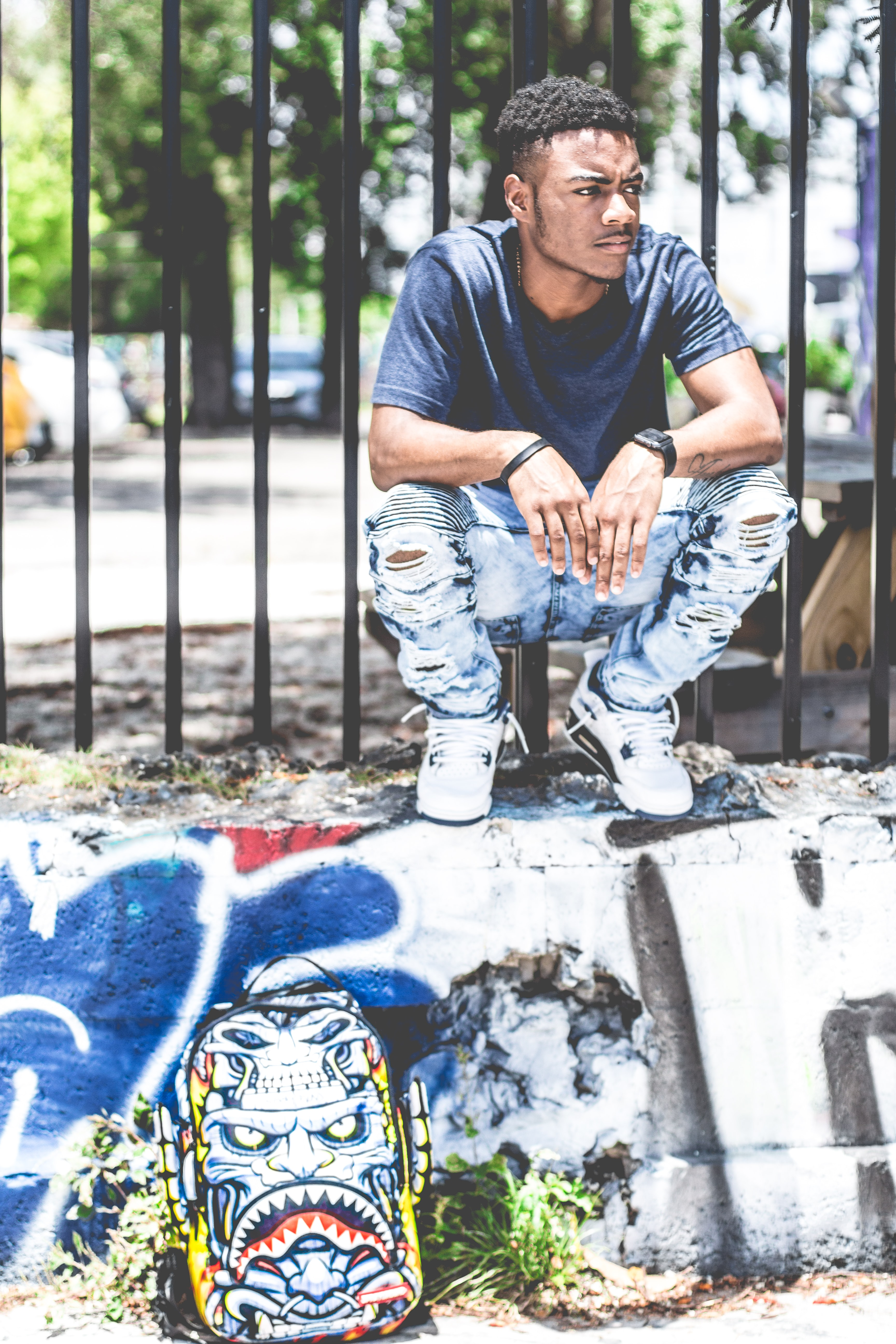 Man wearing urban clothing and watch sitting on a graffitied wall