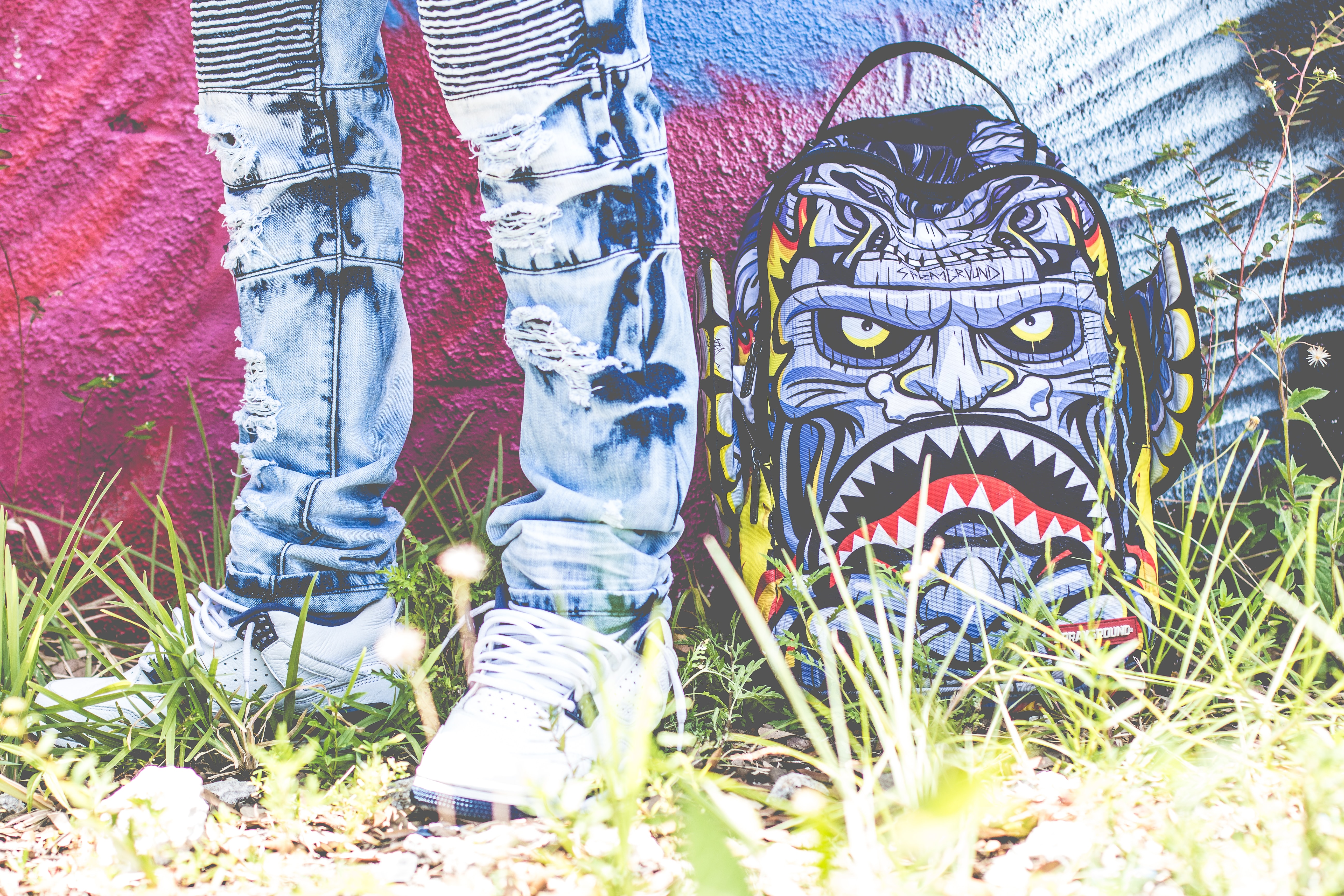 A person standing in front of a piece of graffiti art of a blue monster with sharp triangular teeth.