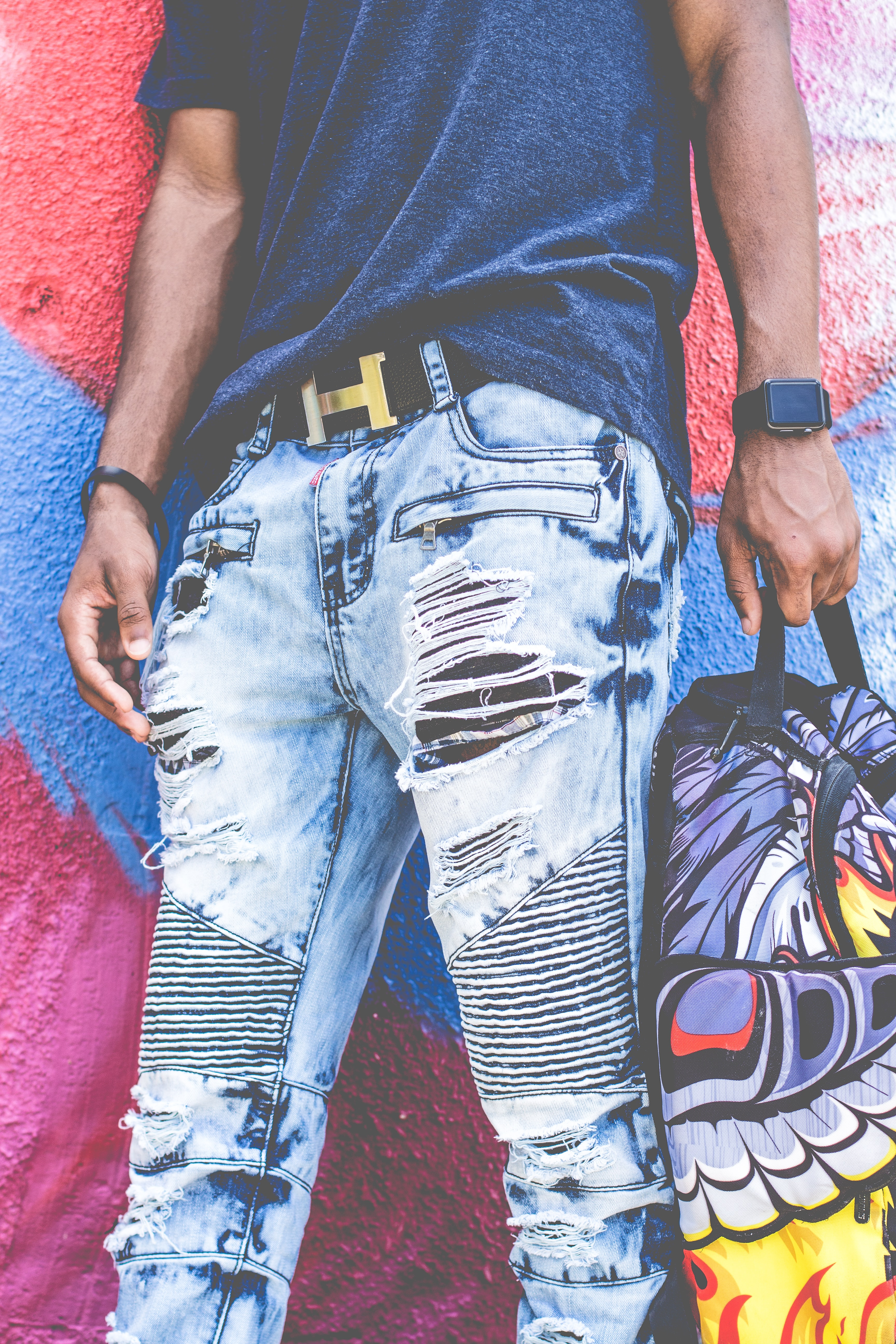 Low shot of person wearing ripped jeans and holding a backpack near a mural