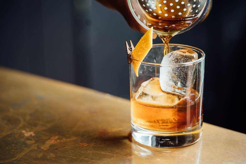 liquor pouring on clear shot glass
