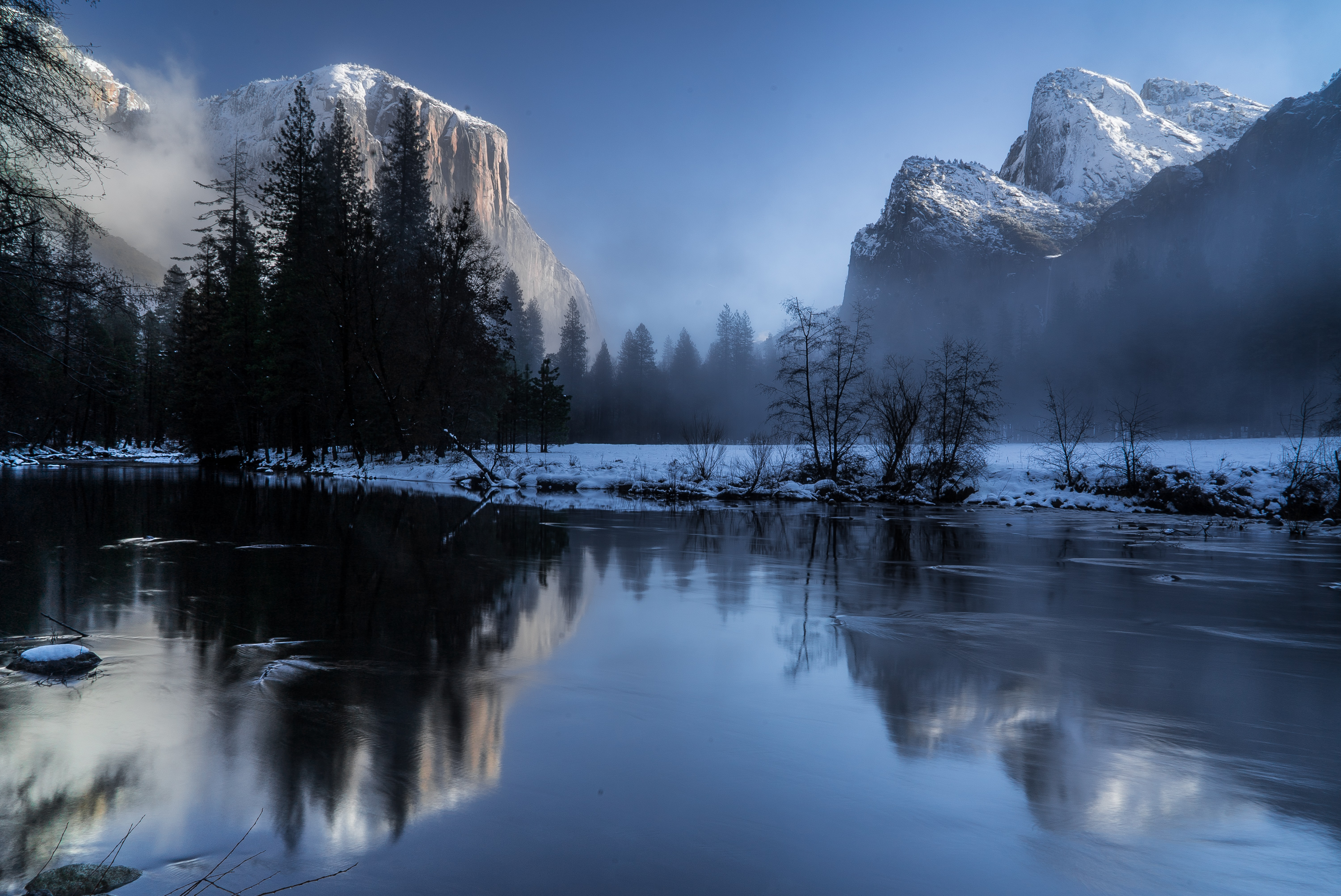 A misty frozen lake with a reflection and view of snow capped mountains in Yosemite Valley