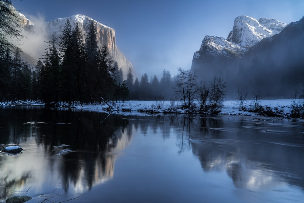reflection of mountains and trees on body of during snow
