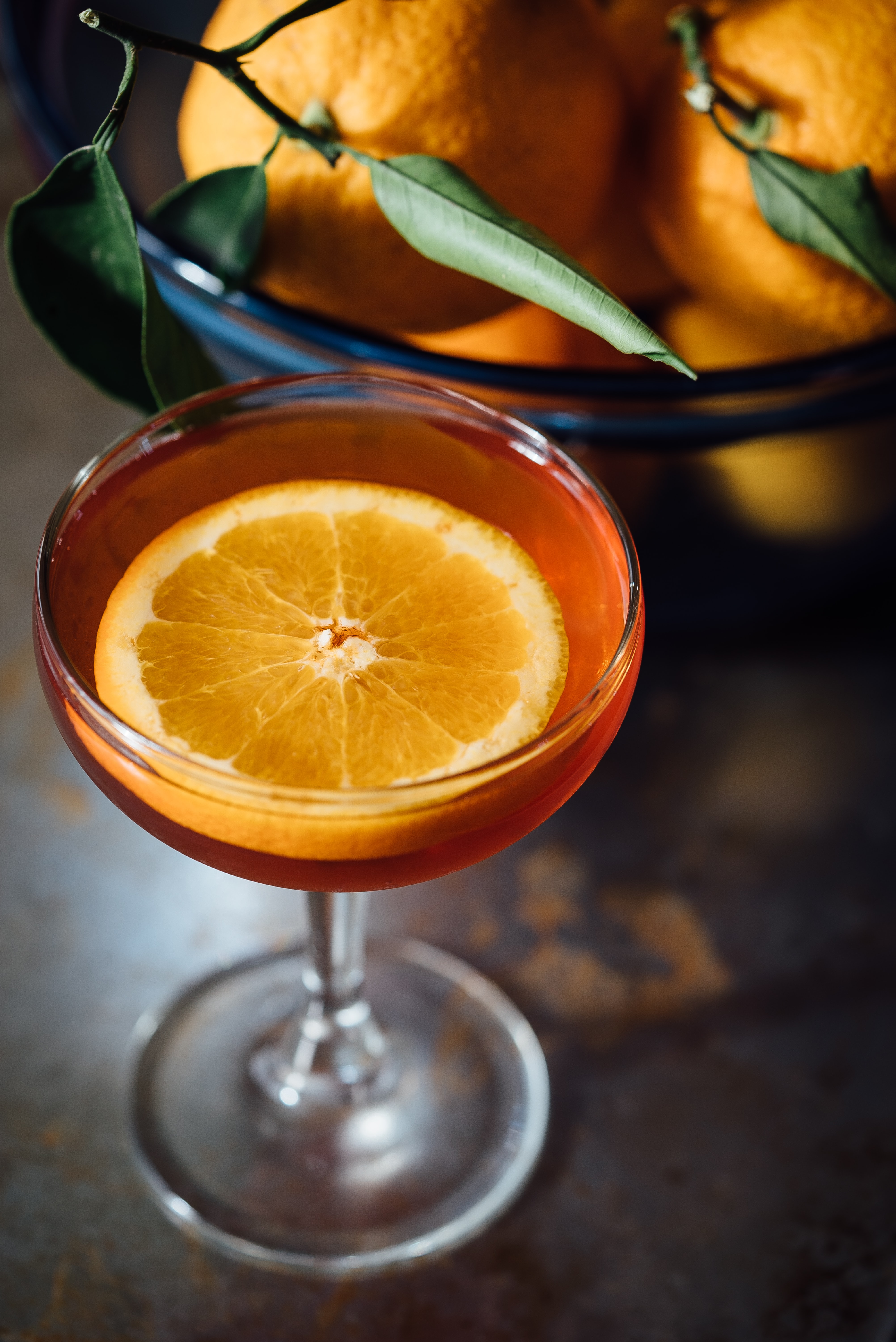 Macro view of a cocktail orange drink with a bowl of oranges with leaves by its side
