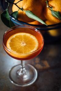 orange slice in a wine glass full of orange liquid