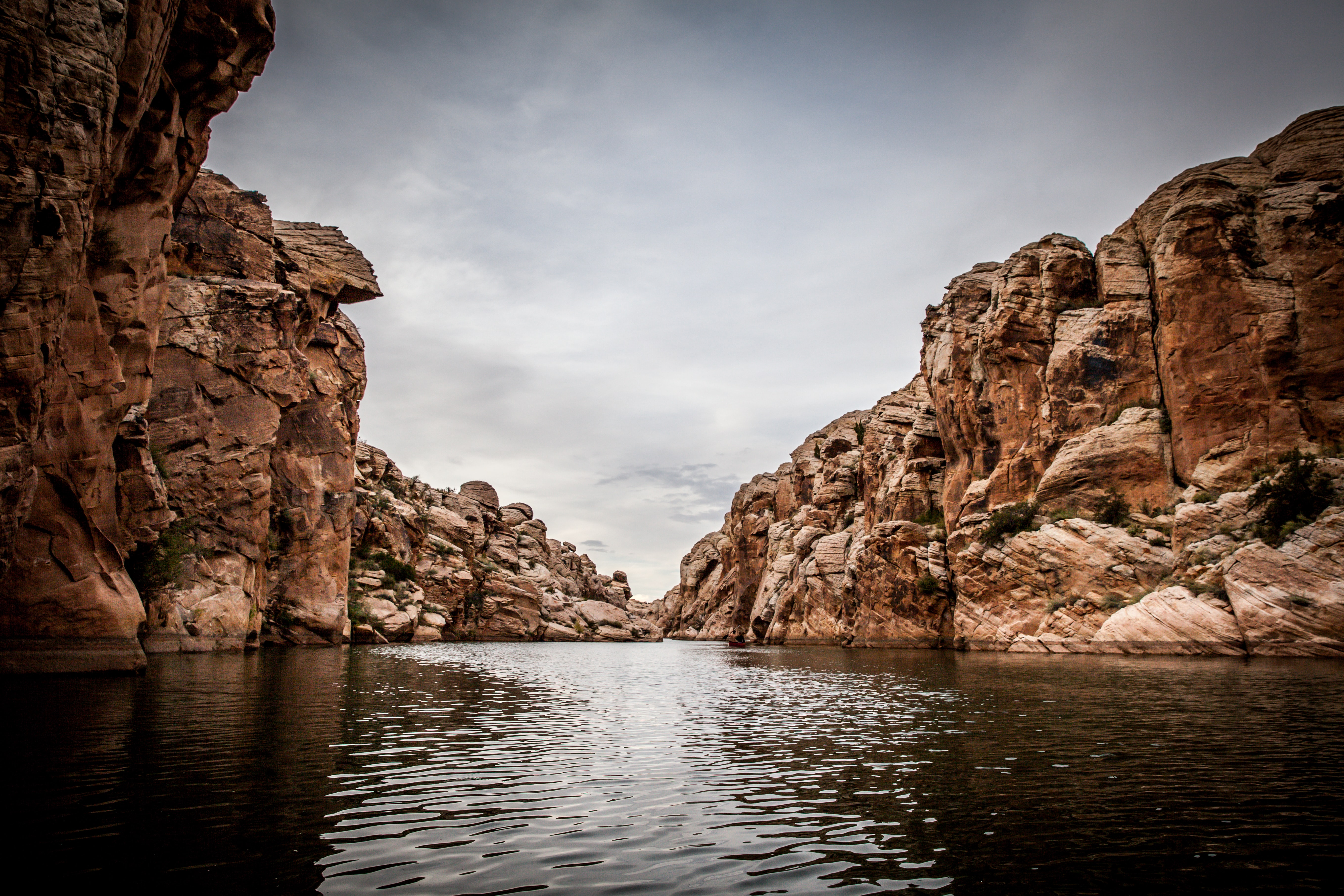 brown cliffs in front of body of water during cloudy sky