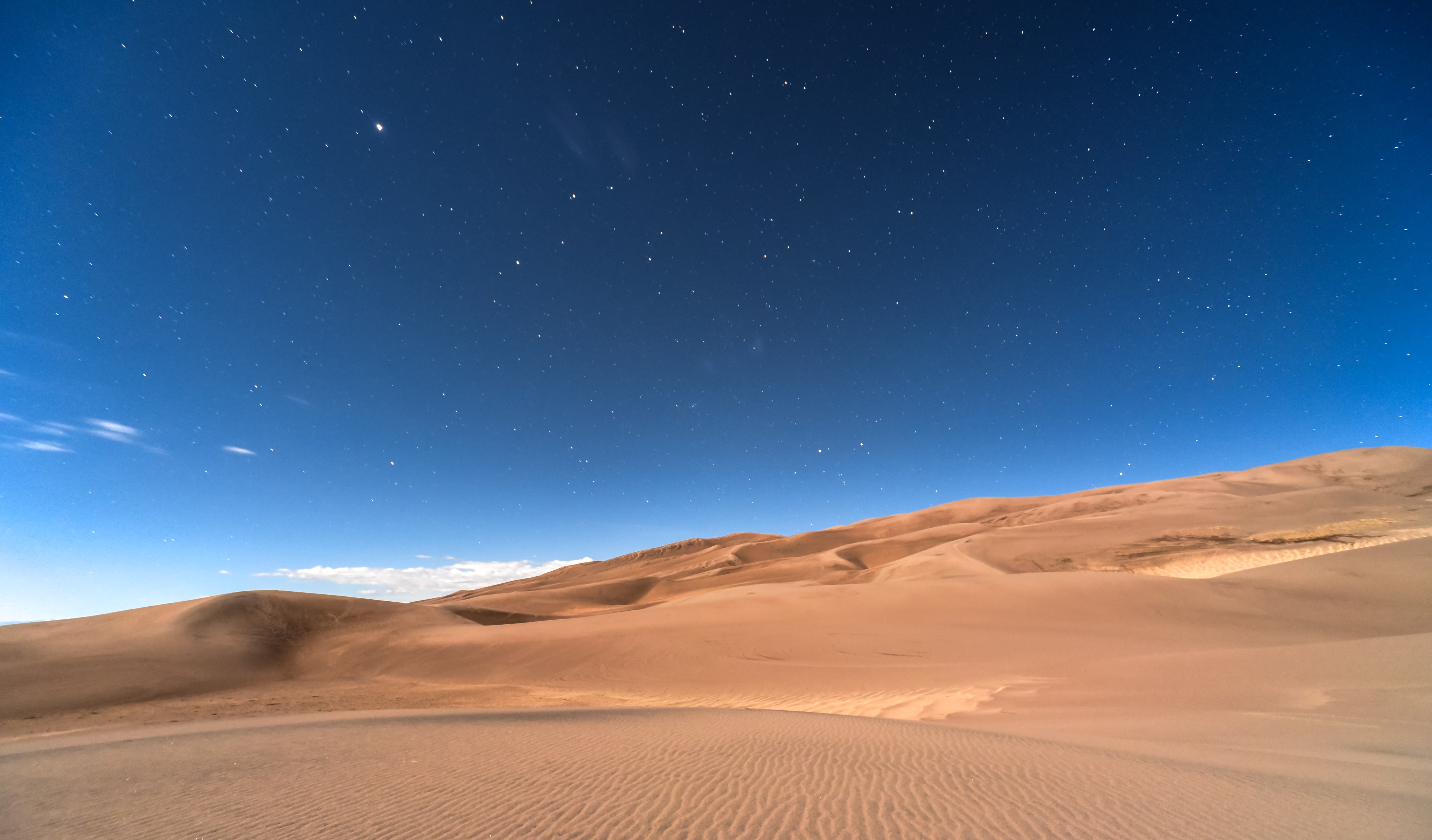 Stars in the clear night sky over a sandy desert in Colorado