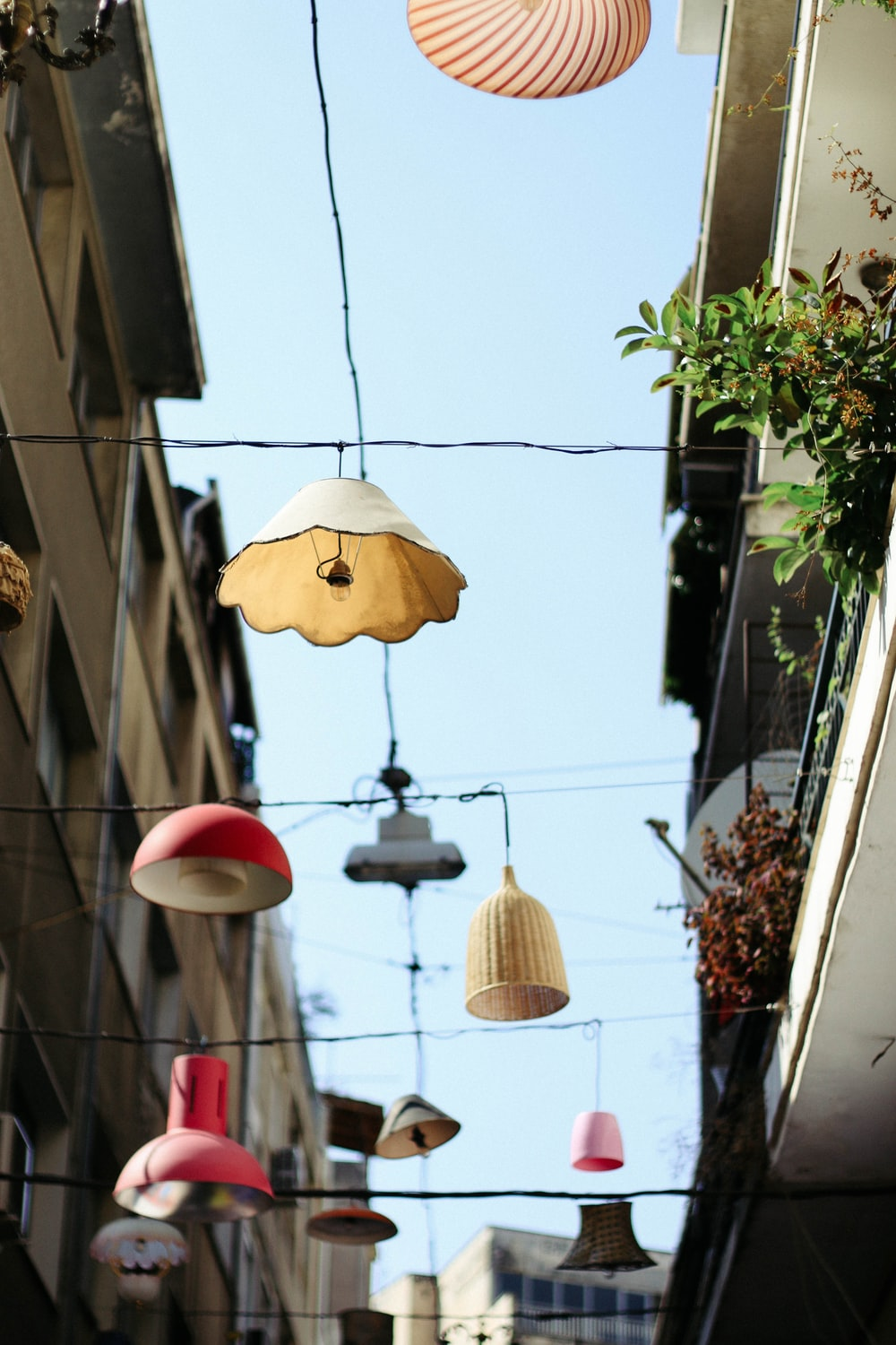 low angle photography of assorted-color lamps hang on wire between white buildings