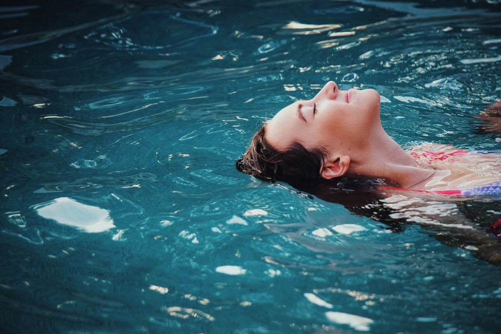 woman floating on body of water