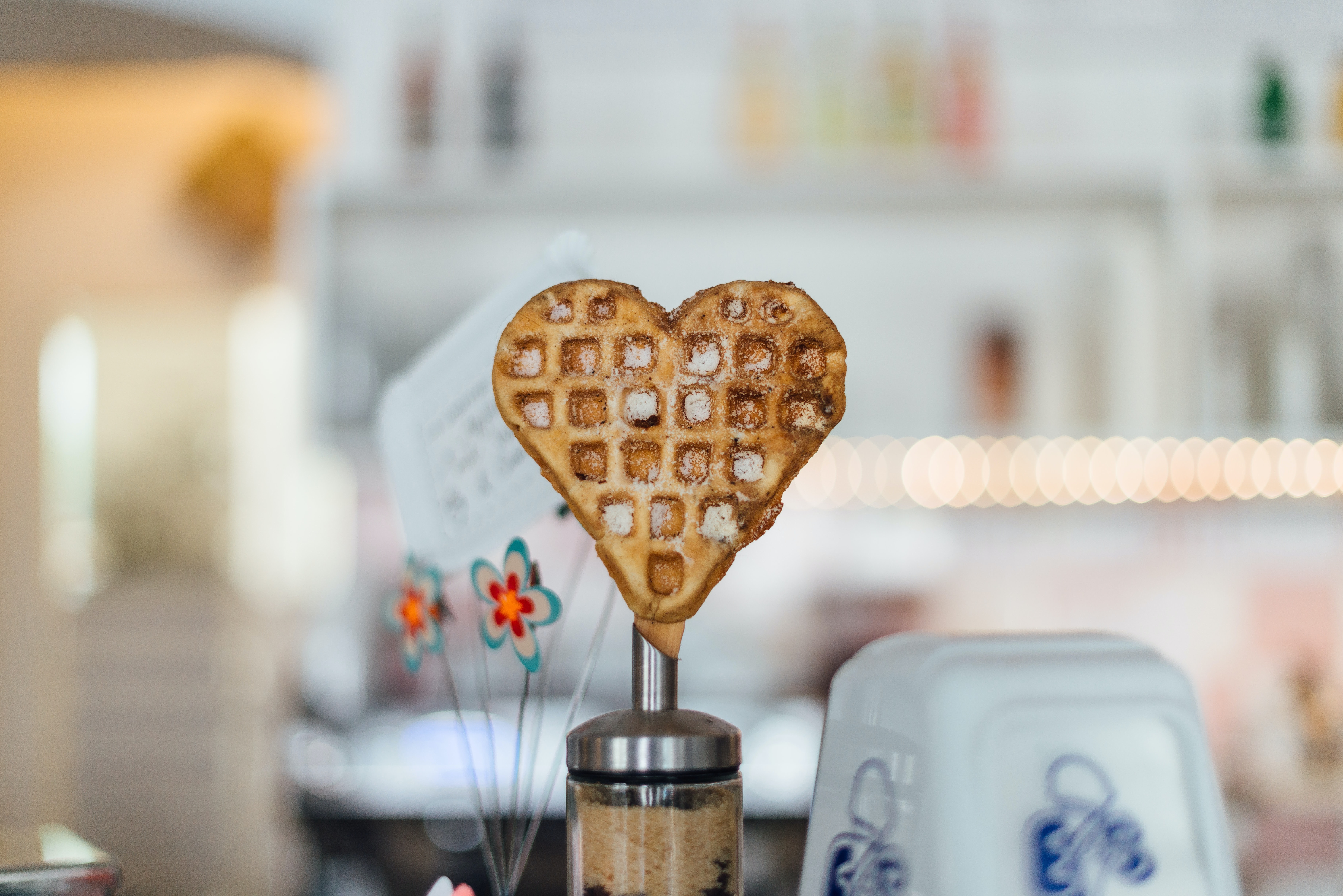 A waffle in the shape of a heart is displayed at a bright shop in Maybachufer