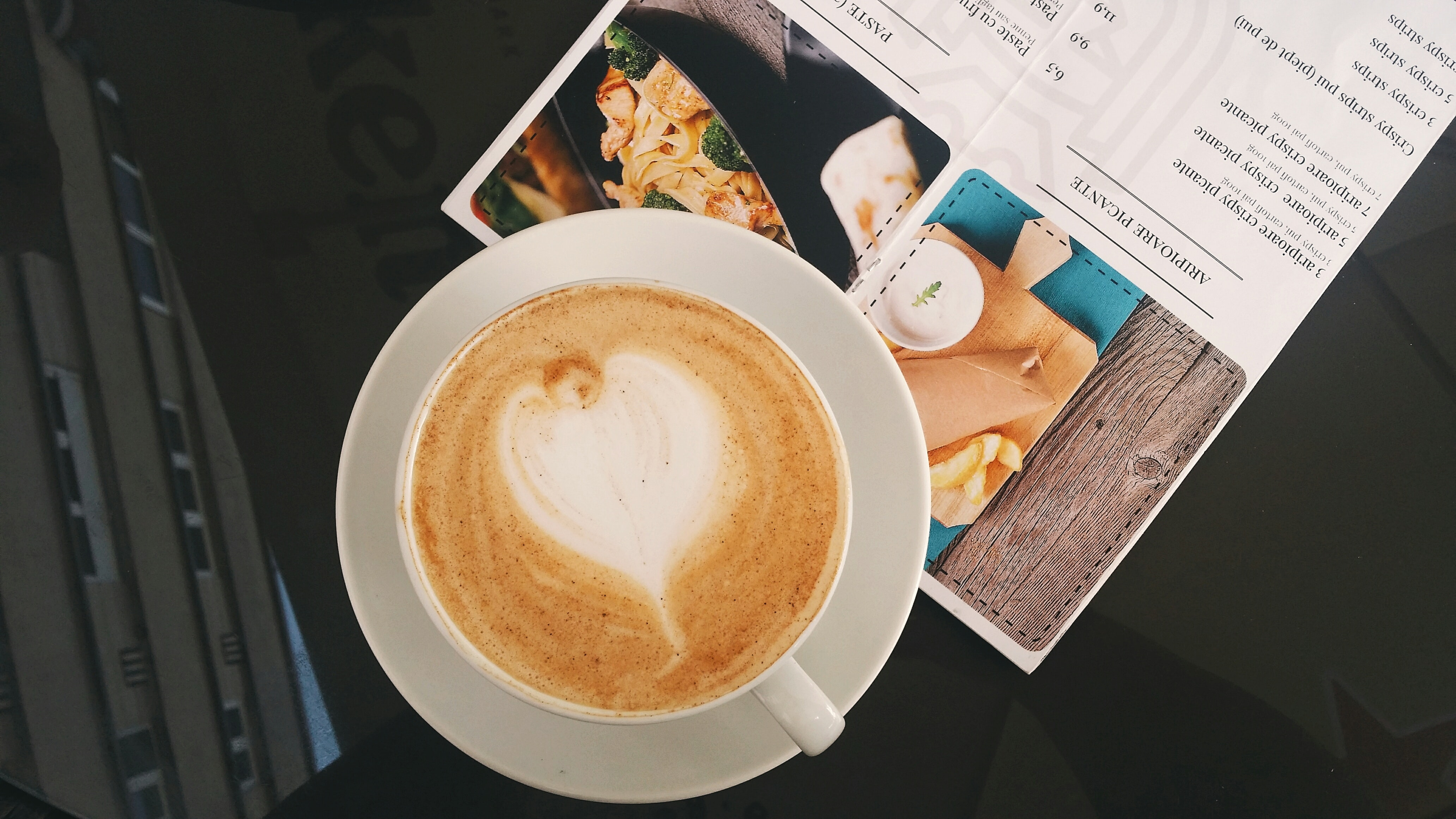 Latte in a white cup and saucer on top of a recipe card on a glass table
