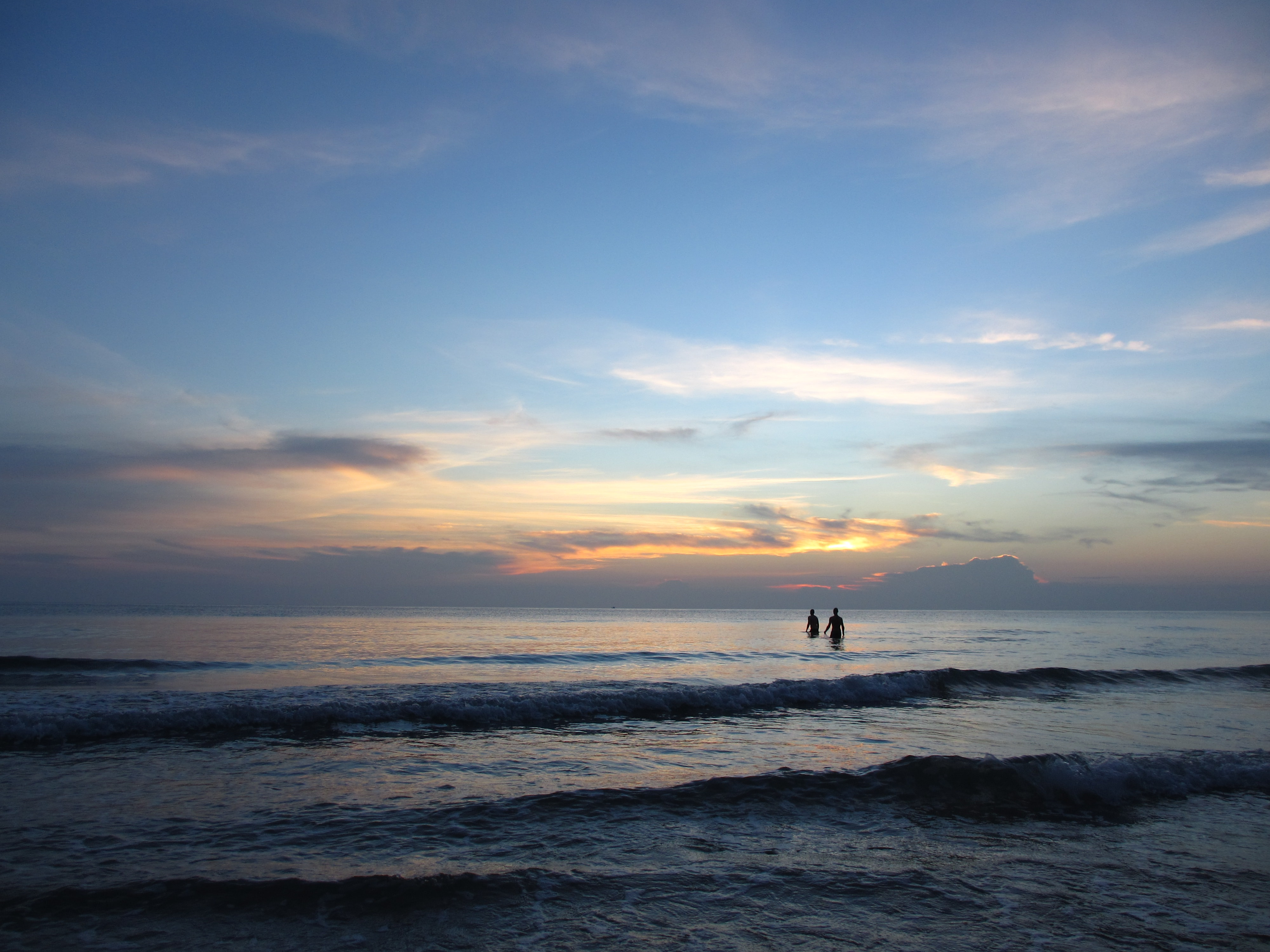 Silhouettes of two people wading through the sea at twilight