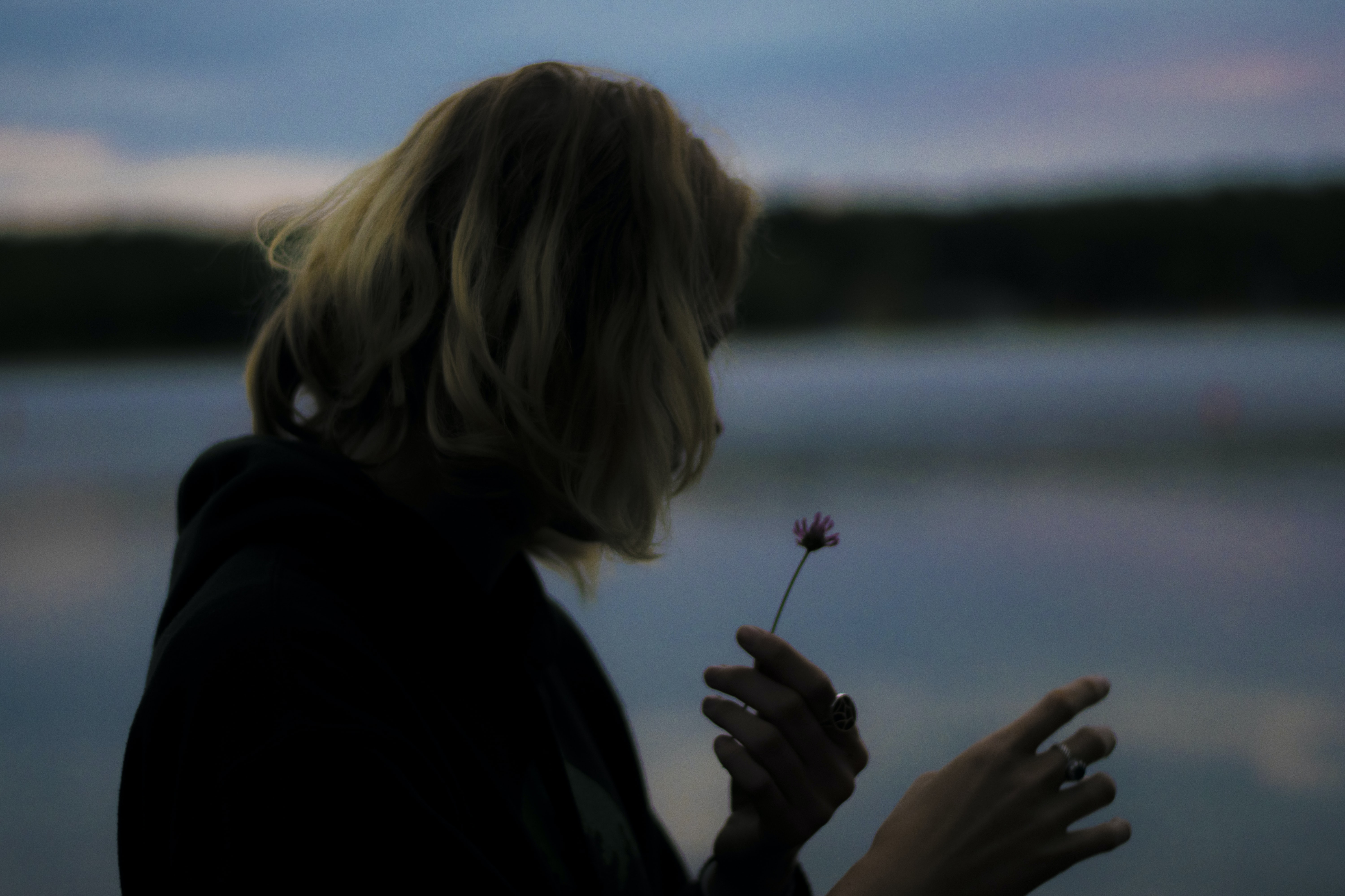 A dim shot of a woman looking at a small pink flower in her hand