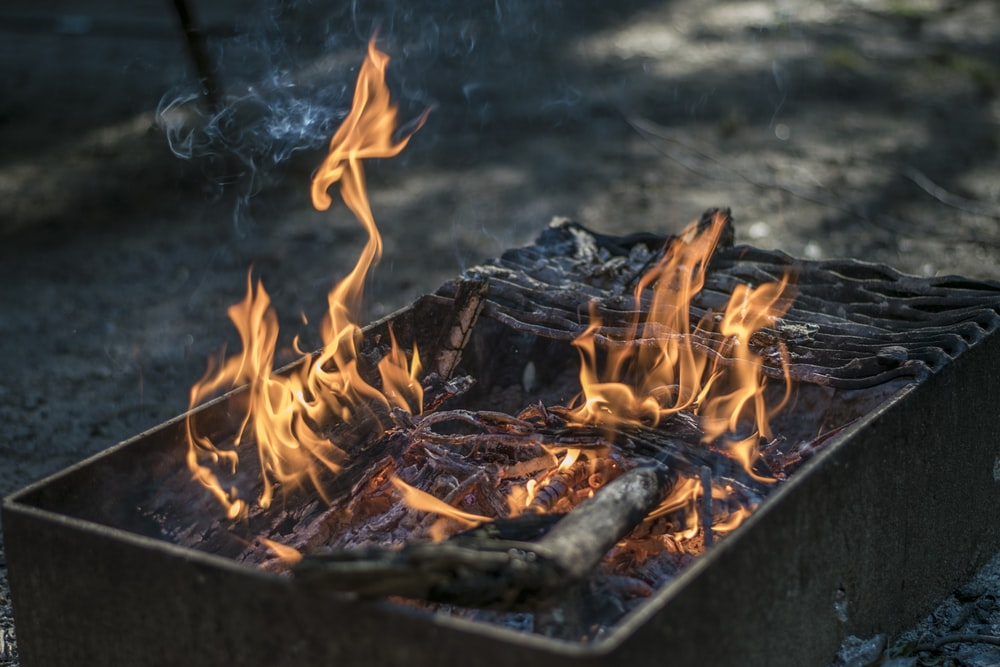 rectangular black fire pit with fire at daytime