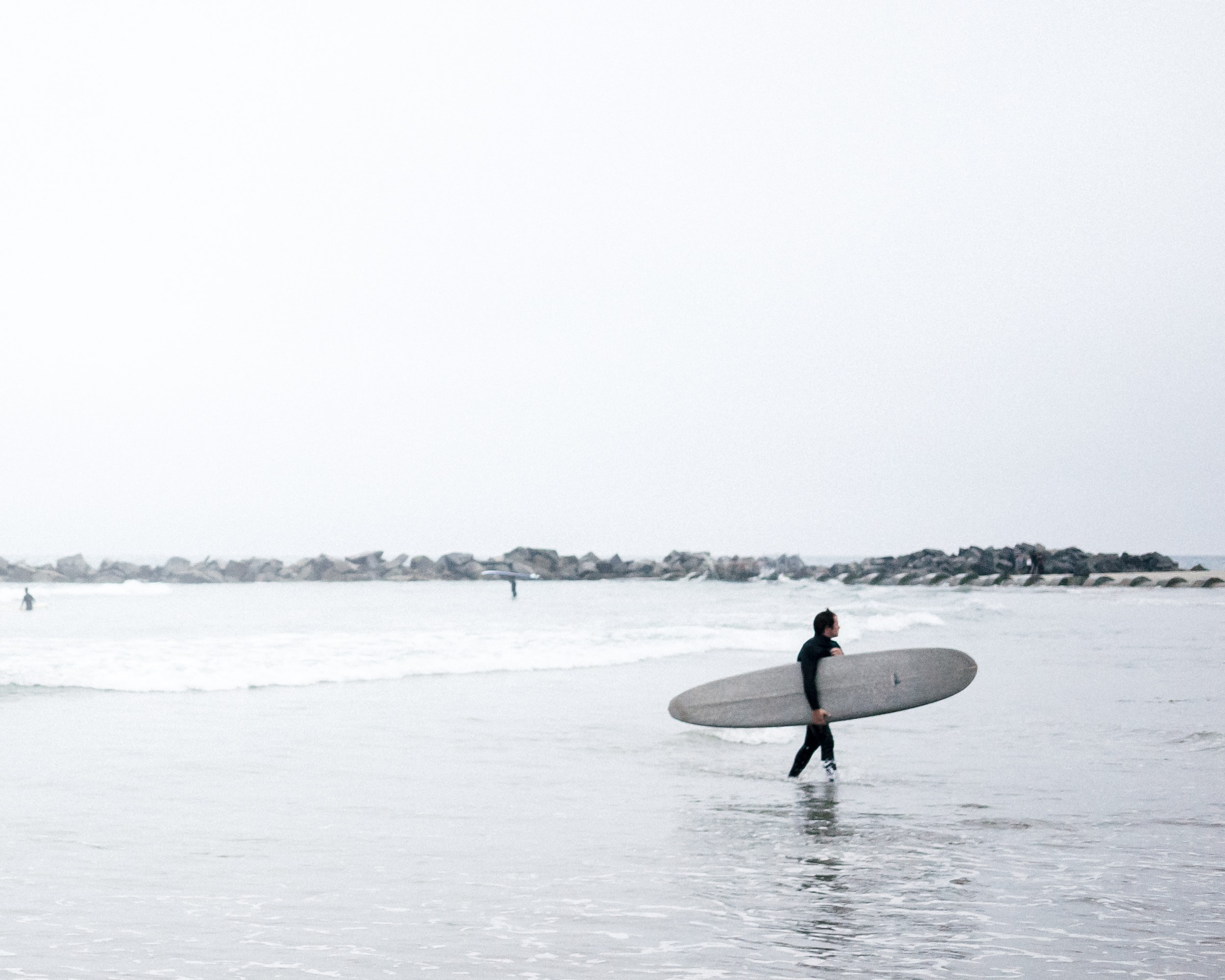 A person walking back to the beach while carrying his water board.