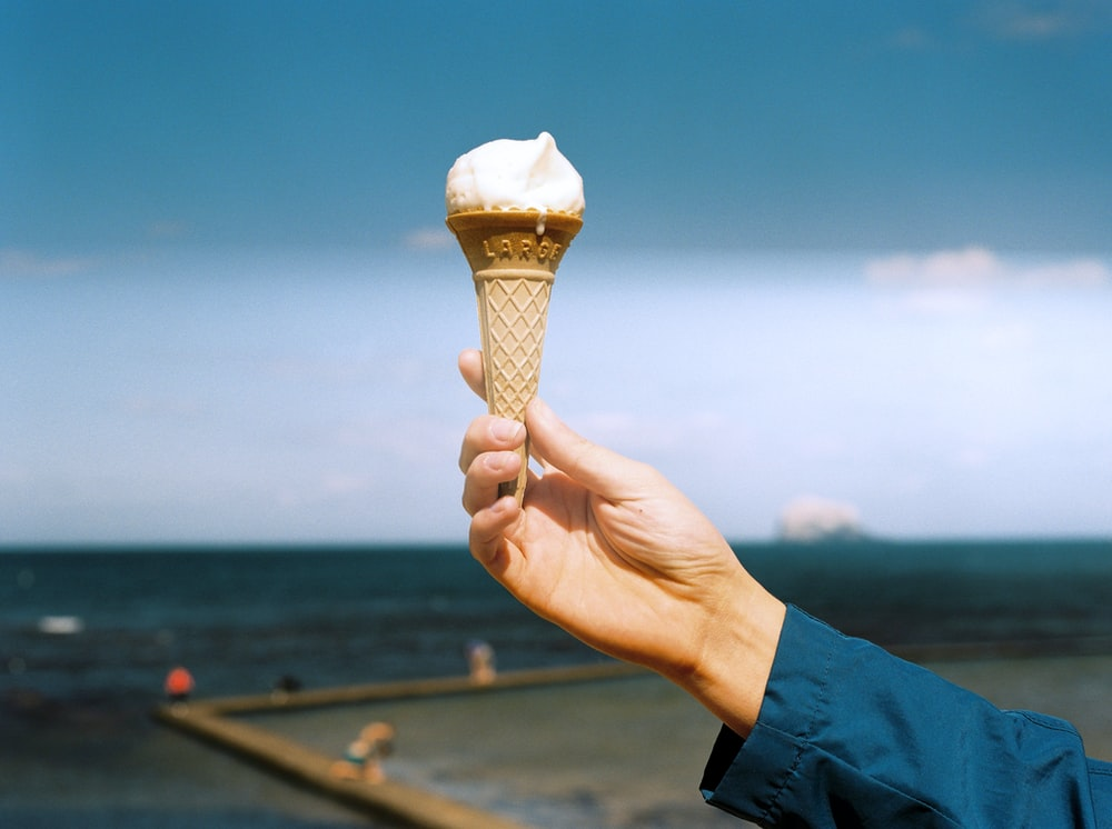 person holding cone with ice cream