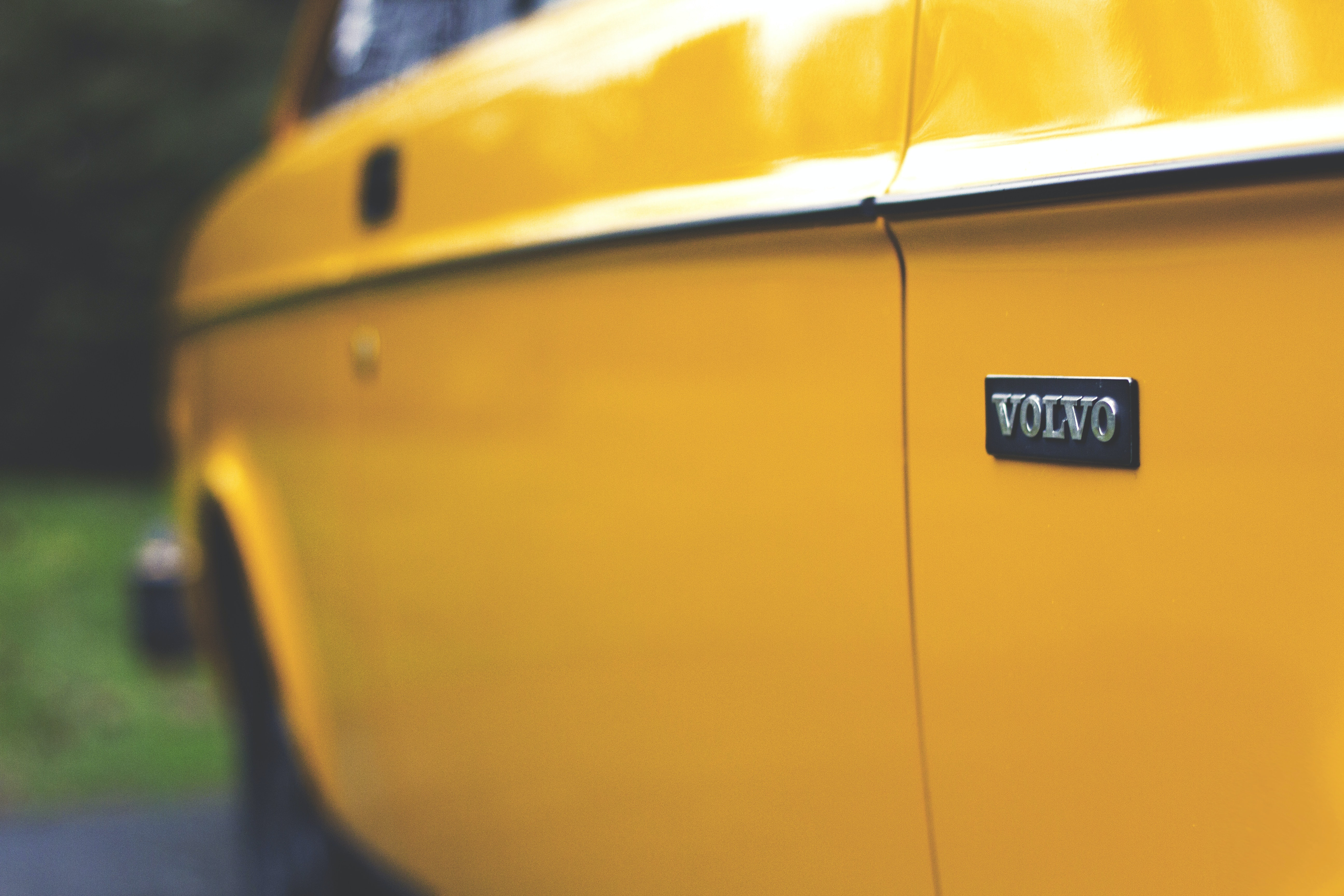 Close up shot of the door of a shiny, yellow, vintage Volvo