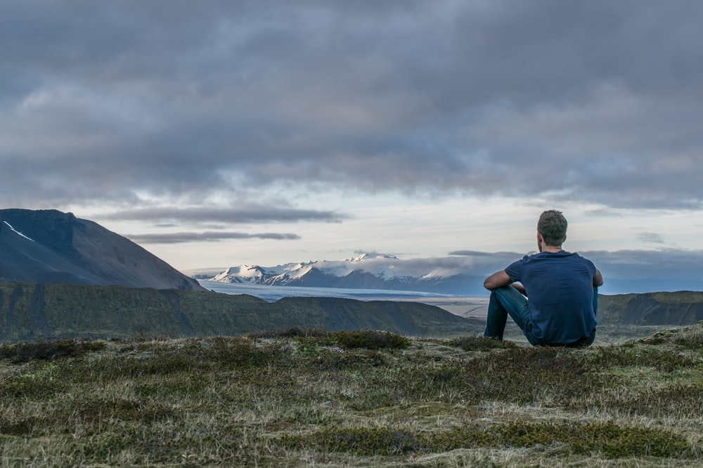man sitting in the top of the mountain