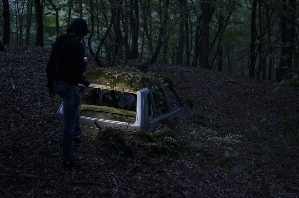 landscape photography of man standing in front of half-buried broken car at forest