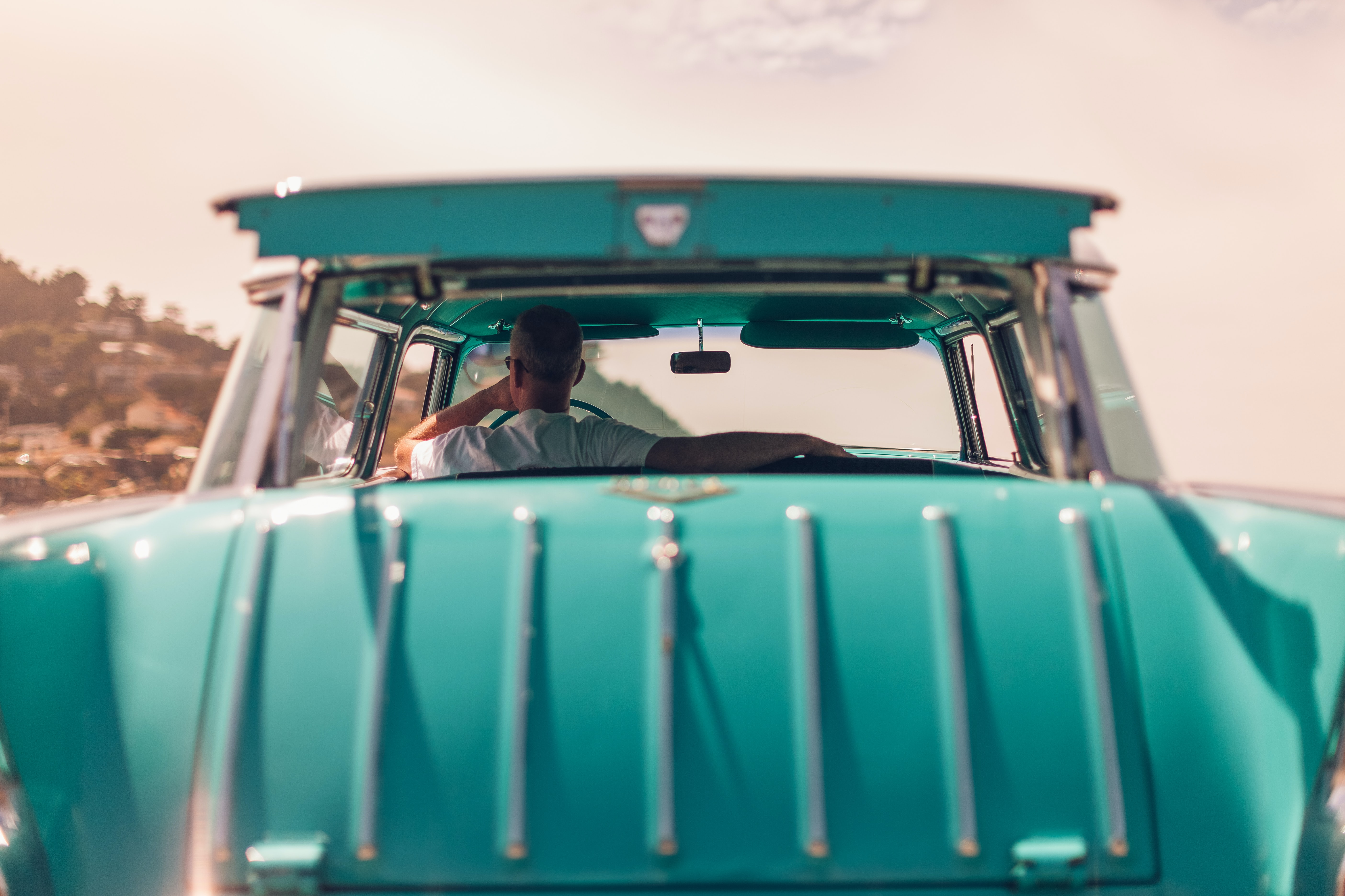 Man sitting in stylish teal classic car looking out window during daytime