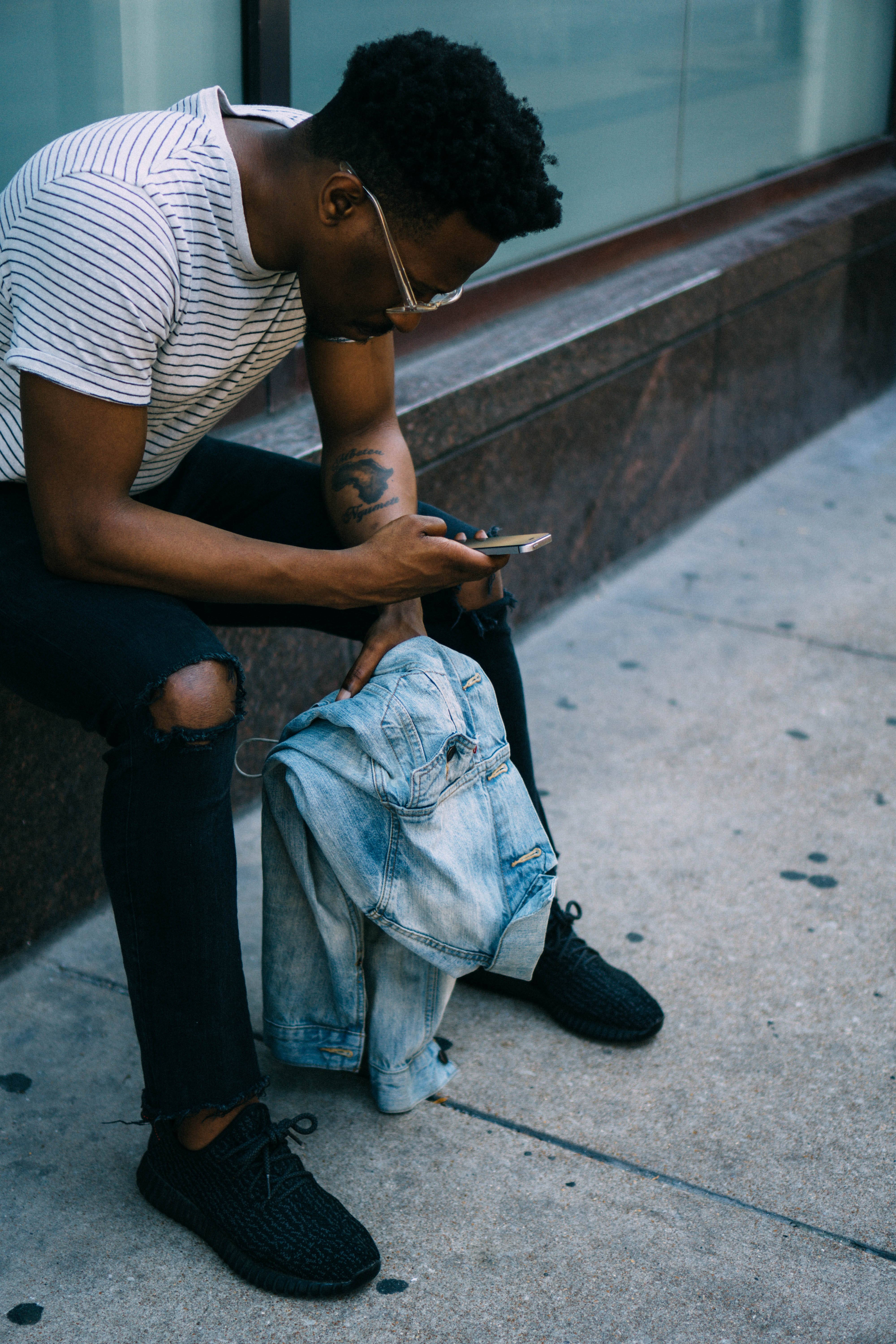 A man wearing a striped shirt and ripped jeans, sitting on a ledge, playing with his cellphone