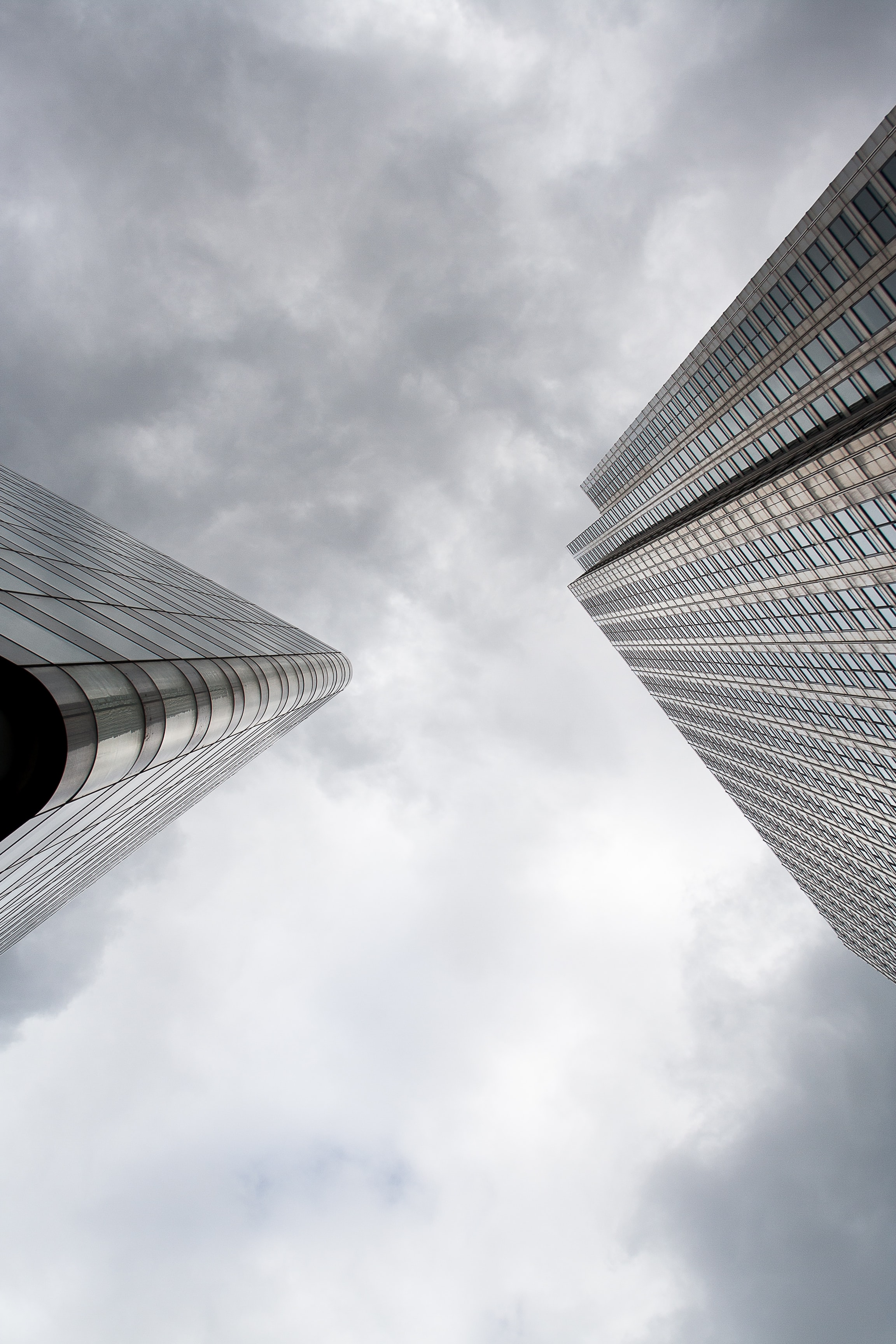 A low-angle shot of the corners of two skyscrapers against a cloudy sky
