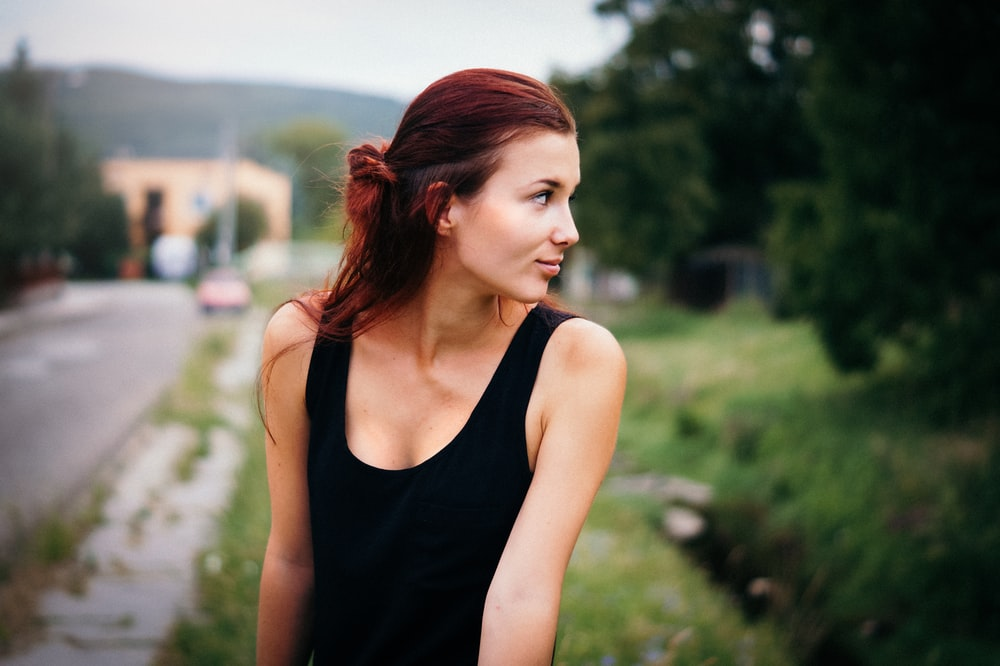 depth of field photography of woman in black tank top on street