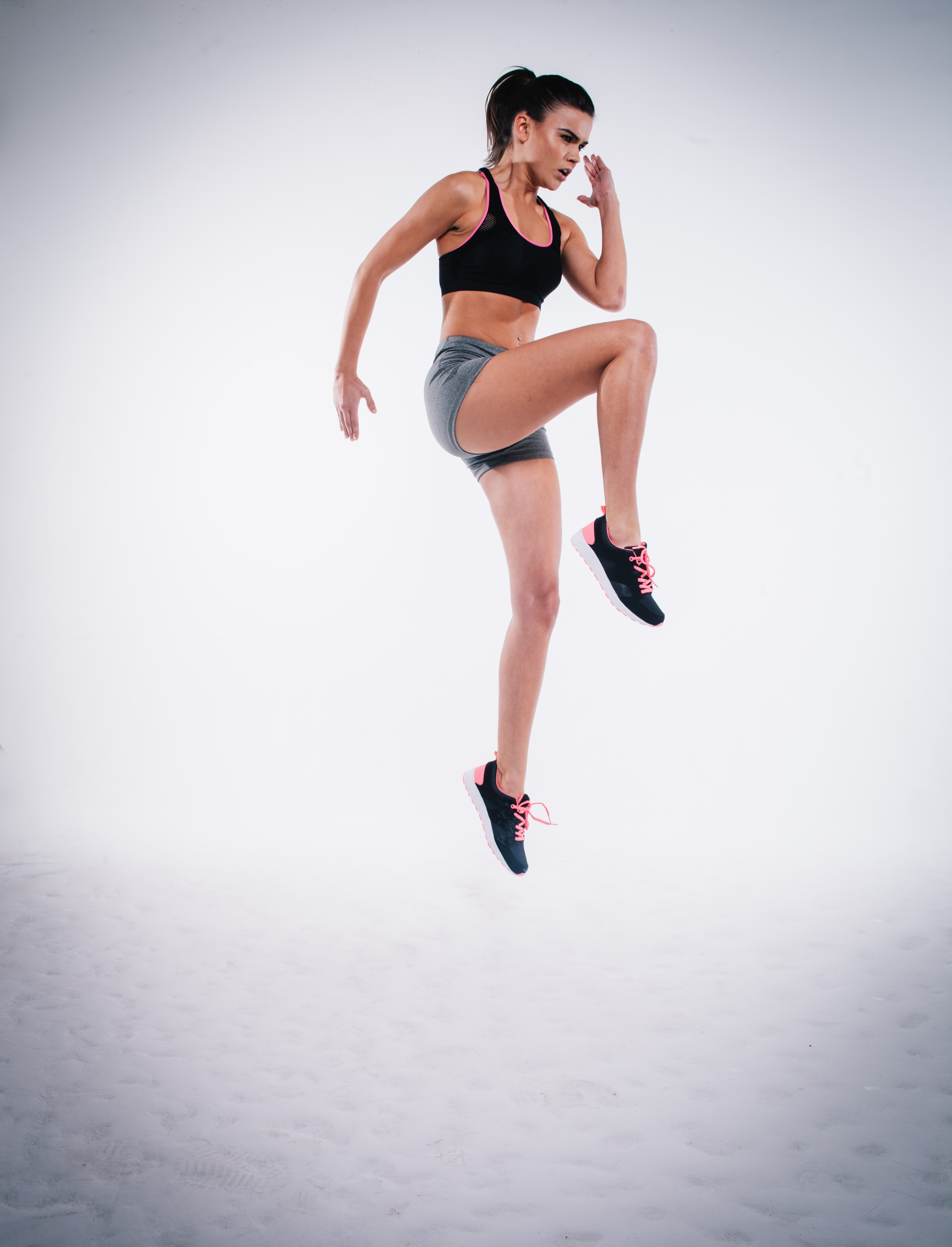 A determined woman in a sports bra, jump-lunging into the sky in London