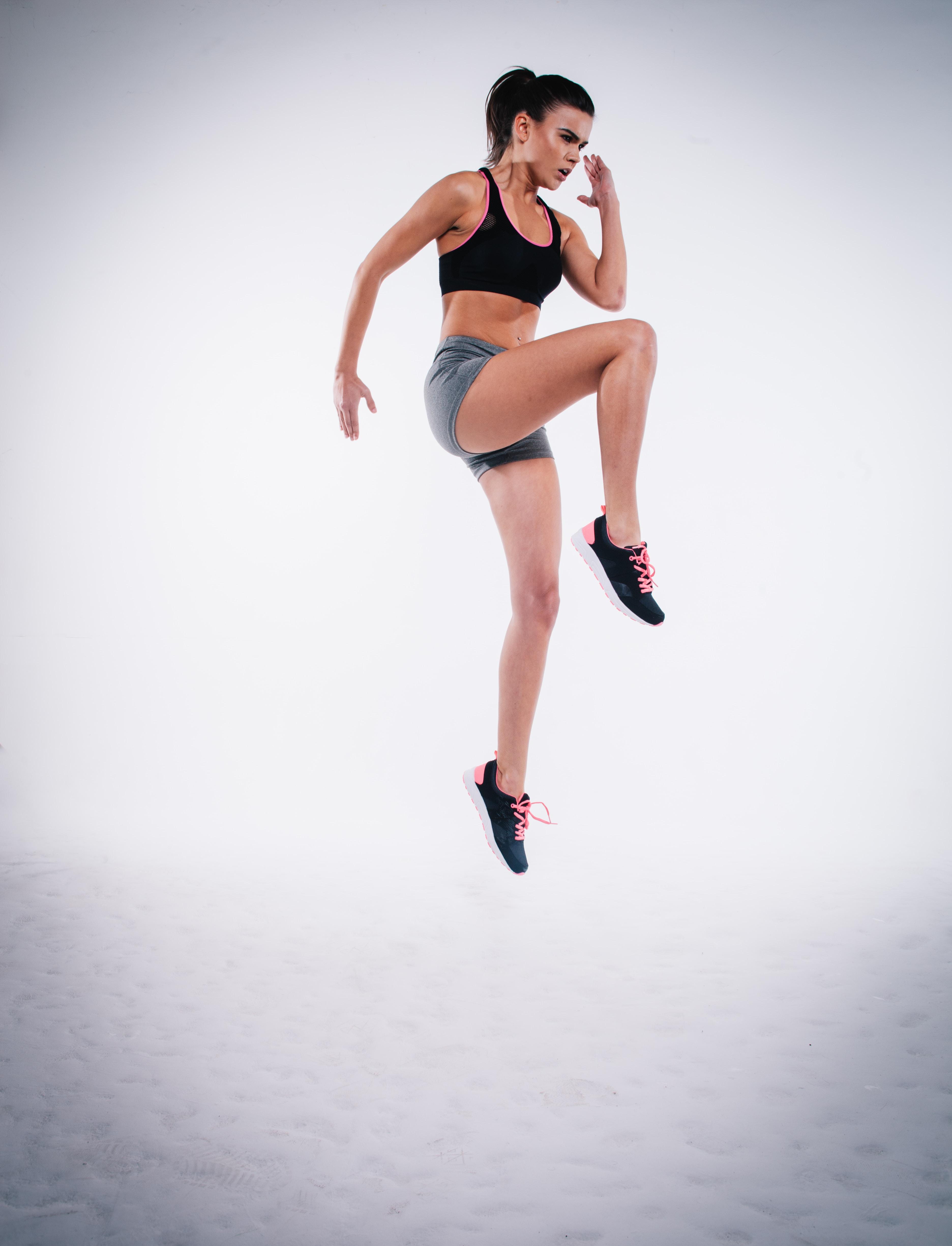 woman jumping near white wall paint