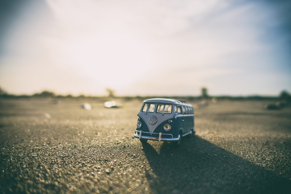 shallow focus photography of white and teal die-cast Volkswagen Samba with sunlight