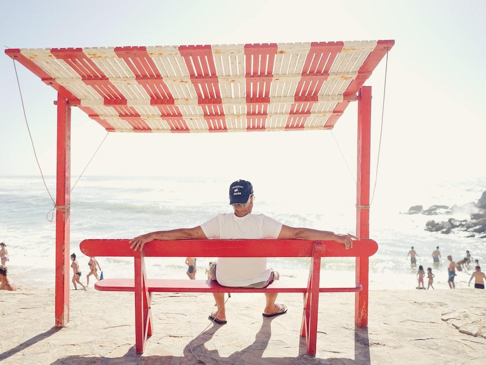 man sitting on bench near beach