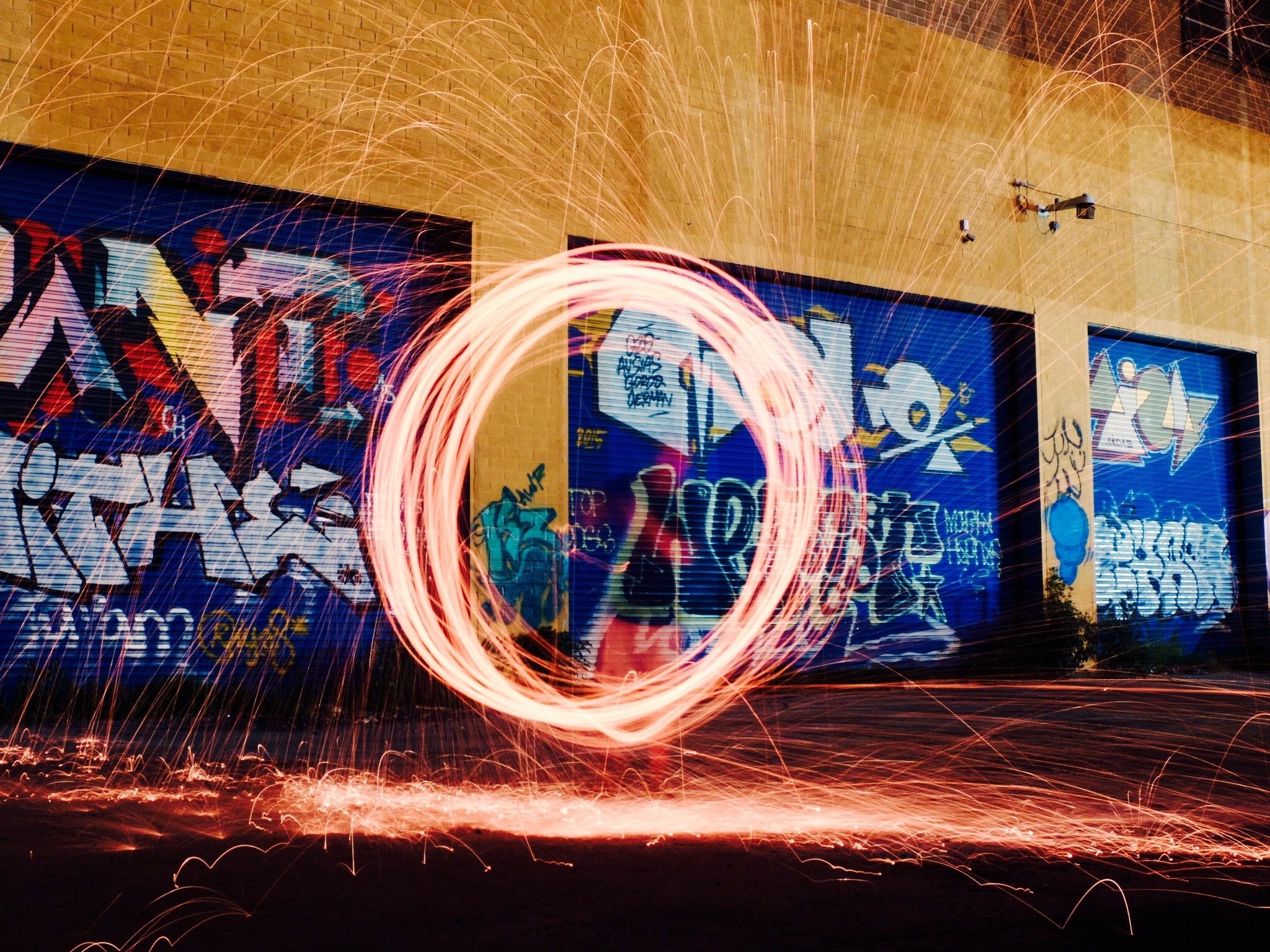 A firework light painting shot with wire wool taken in front of a building marked in graffiti
