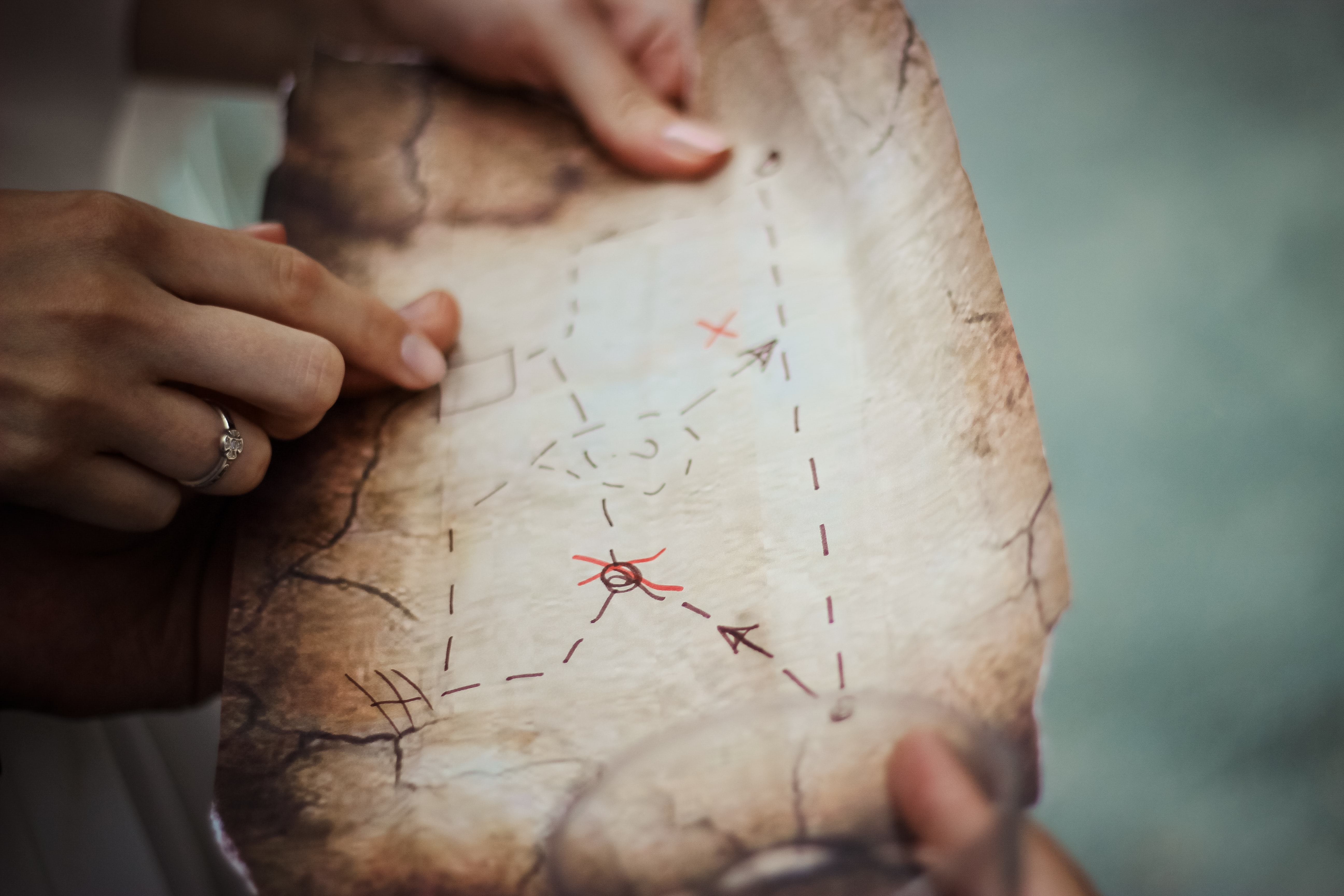 Two people holding up an old map with directions and X marks drawn with a marker