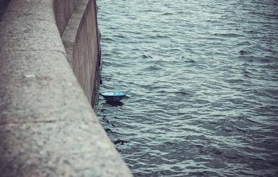 blue umbrella on body of water