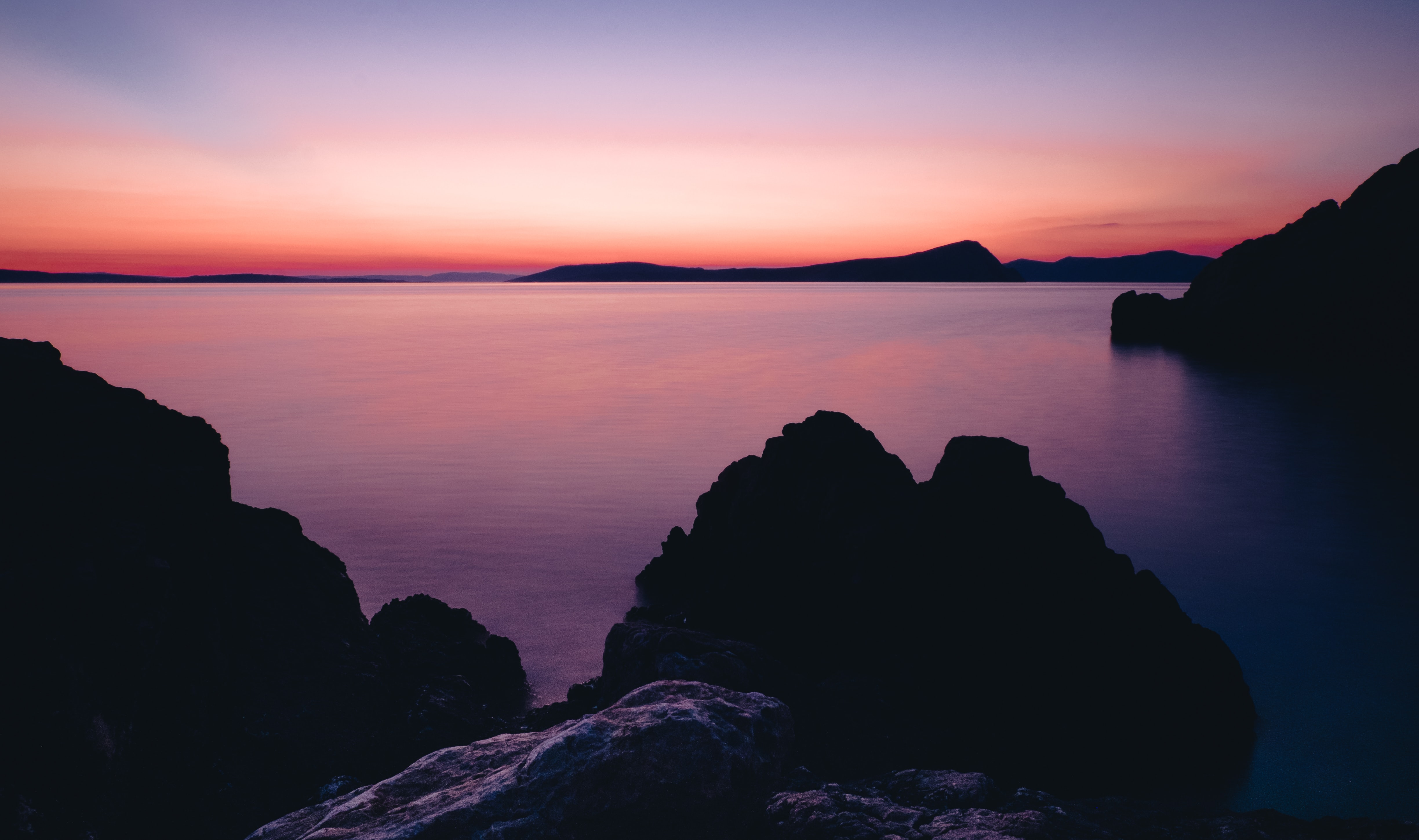 Placid waters under a pink and purple sky, with rocky coasts along the water