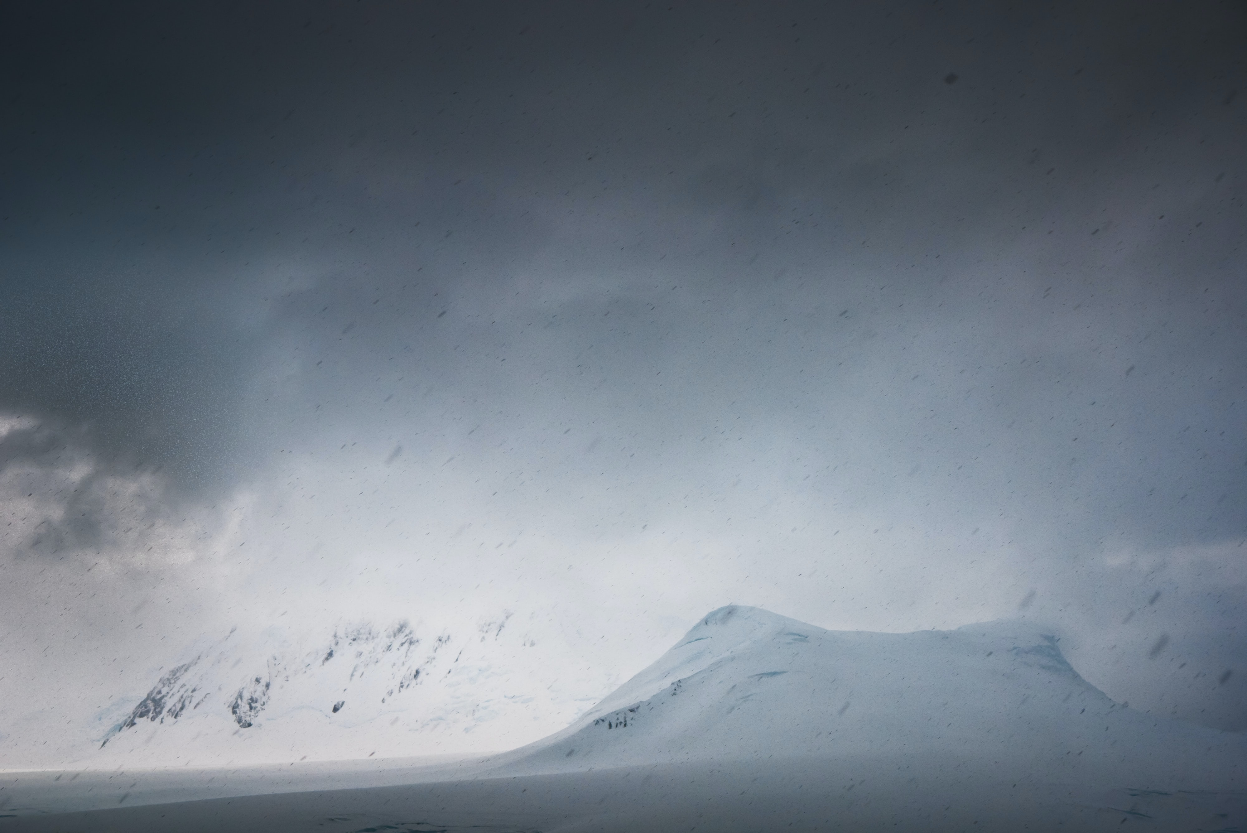Dark storm clouds roll in over snowy mountains