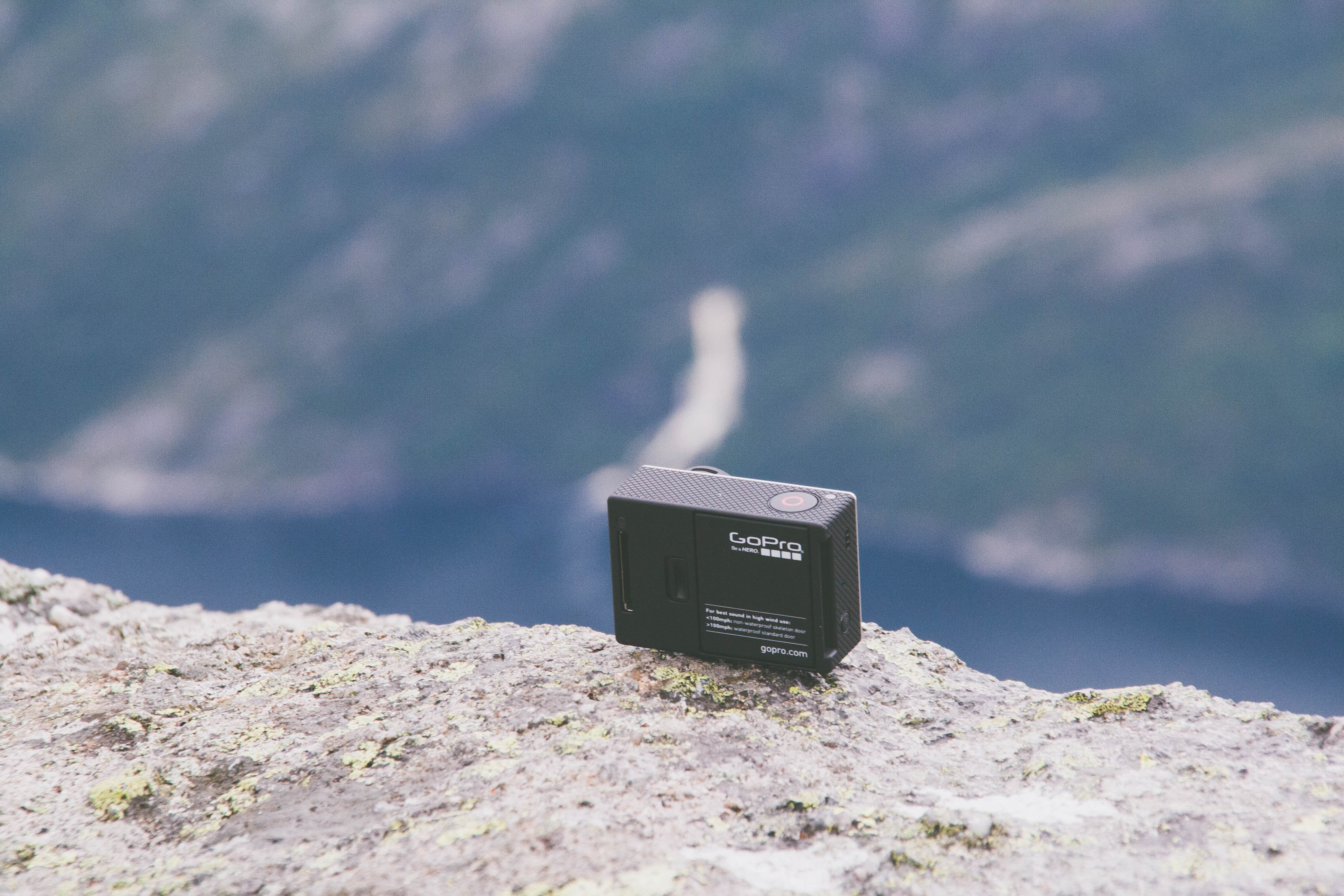 A GoPro camera sitting on a mountain cliff.